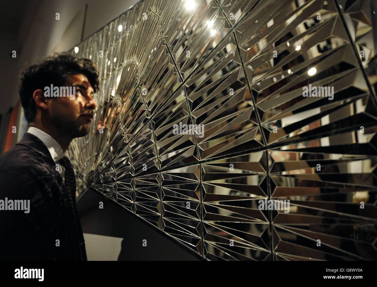 Un empleado de Sotheby examina Untitled (Faravahar Wings, Zaratustra) de Monir Shahroudy Farmanfarmaian, que se calcula entre £100.000 y 120.000 libras esterlinas, durante una llamada fotográfica para su próxima venta de un milenio de arte de Oriente Medio en New Bond Street en Londres. Foto de stock