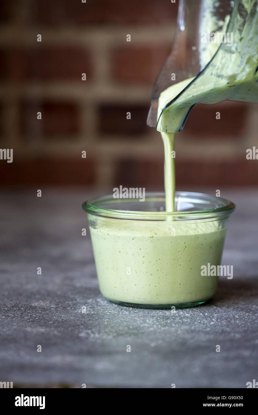 Una persona es verter la salsa de castañas de cajú verde en un recipiente transparente. Imagen De Stock