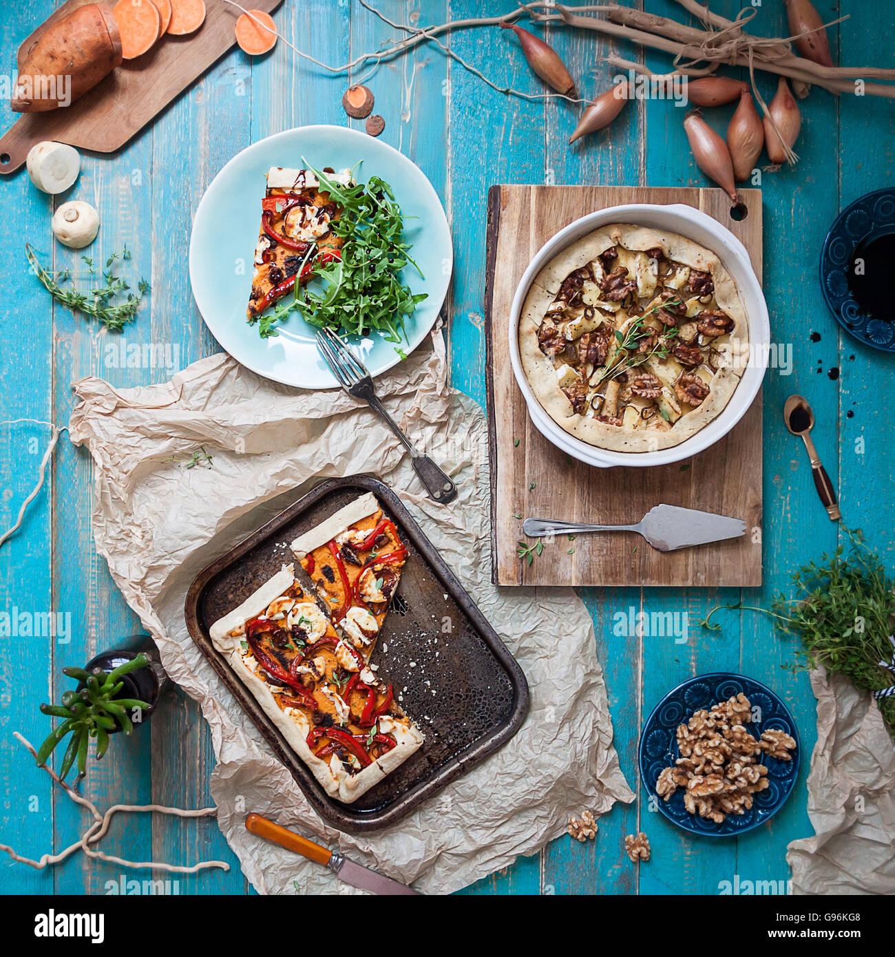 Vista de tabla flotante superior de sabrosas tartas vegetarianas y varios ingredientes Imagen De Stock