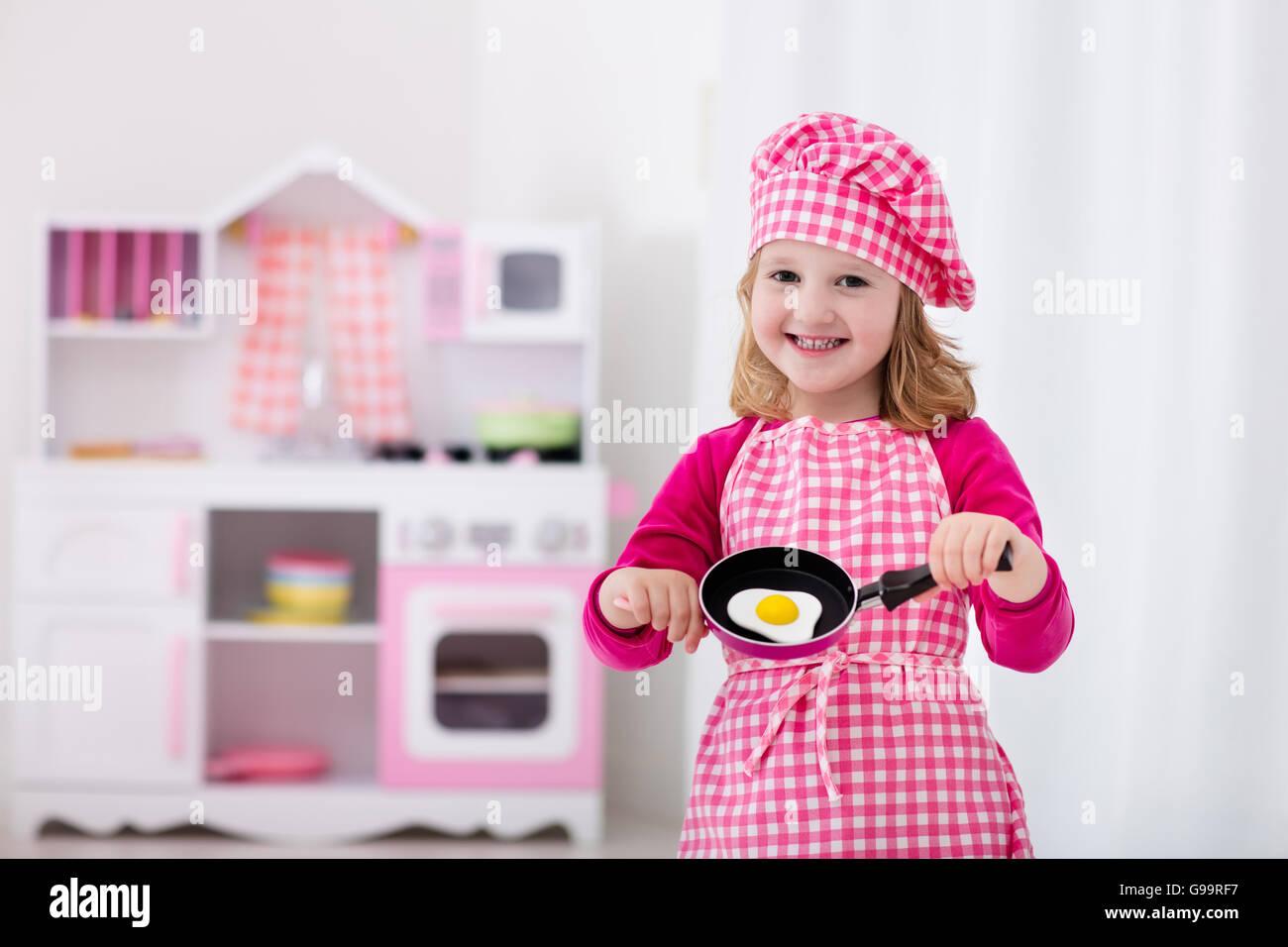 Niña y Niño en chef hat delantal y cocinar en una cocina de juguete ...