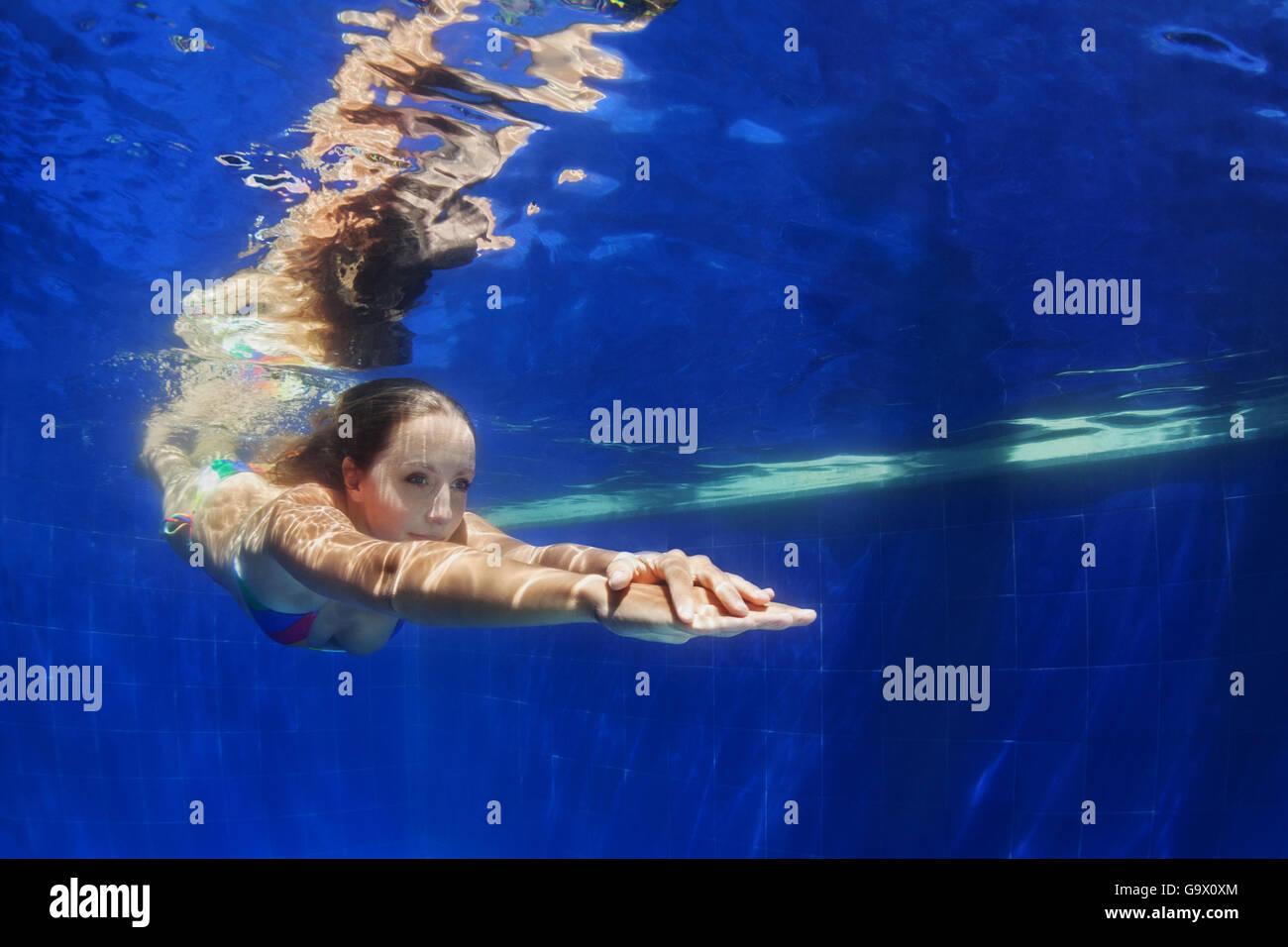 Hermosa joven zambullirse bajo el agua con la diversión de piscina a piscina azul. Estilo de vida activo y Imagen De Stock