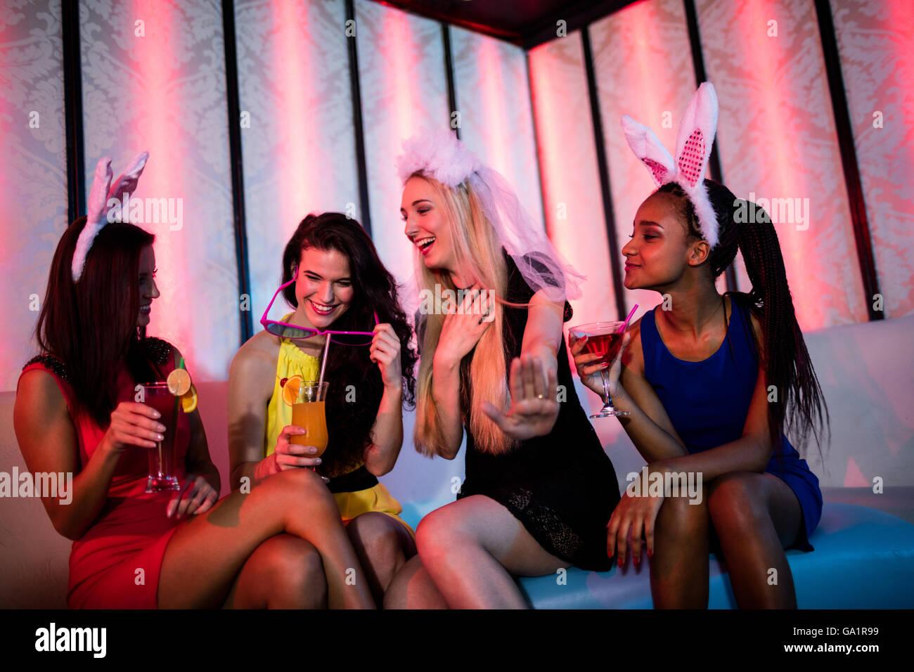 Sonriendo amigos disfrutando mientras habiendo cóctel Imagen De Stock