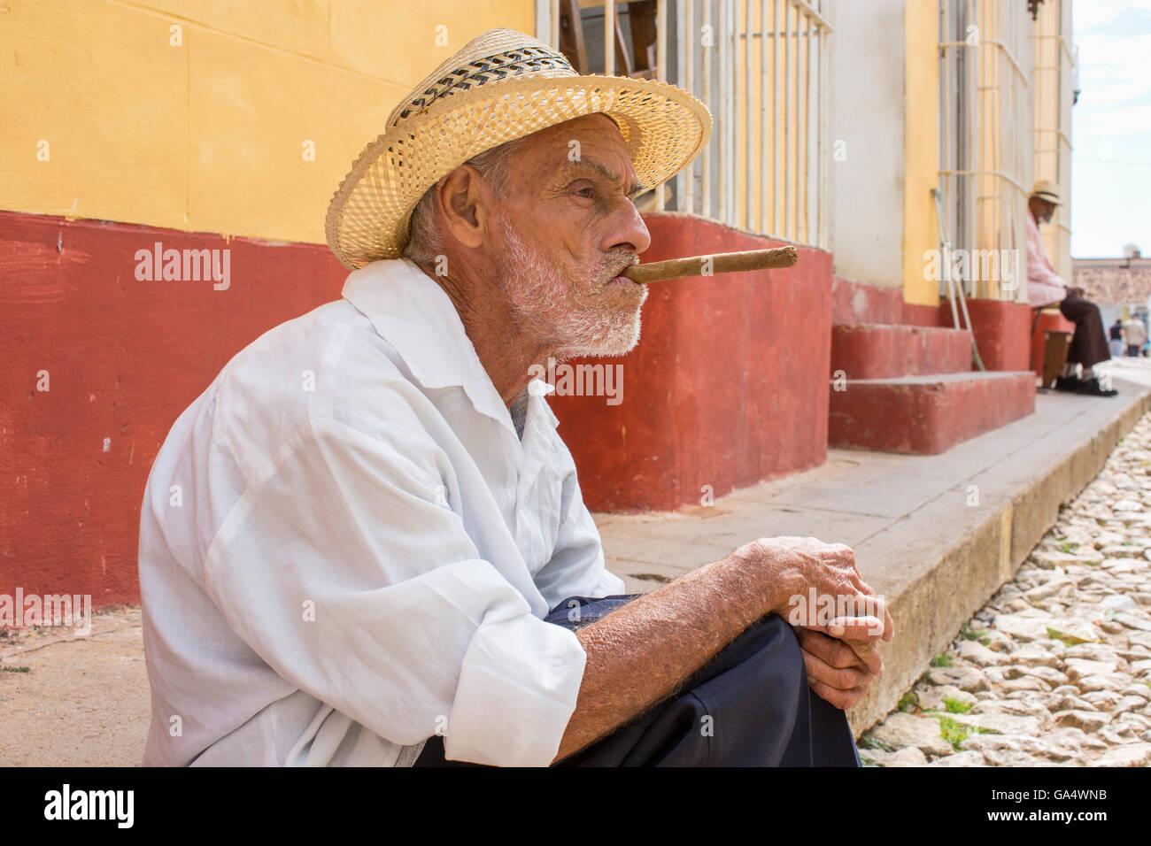 Hombre local en hat con cigarro sentado en la acera de la Plaza Mayor, Trinidad, Cuba Imagen De Stock