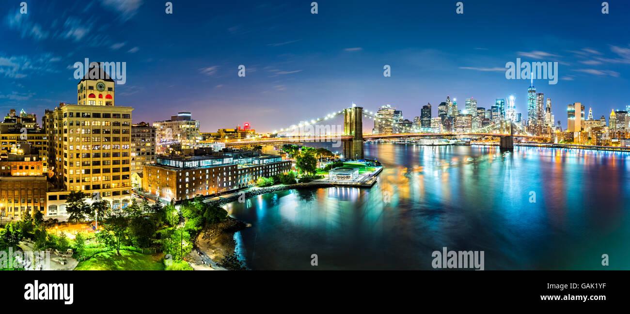 Panorama de la ciudad de Nueva York por la noche. Puente de Brooklyn abarca East River que une Manhattan y Brooklyn Imagen De Stock