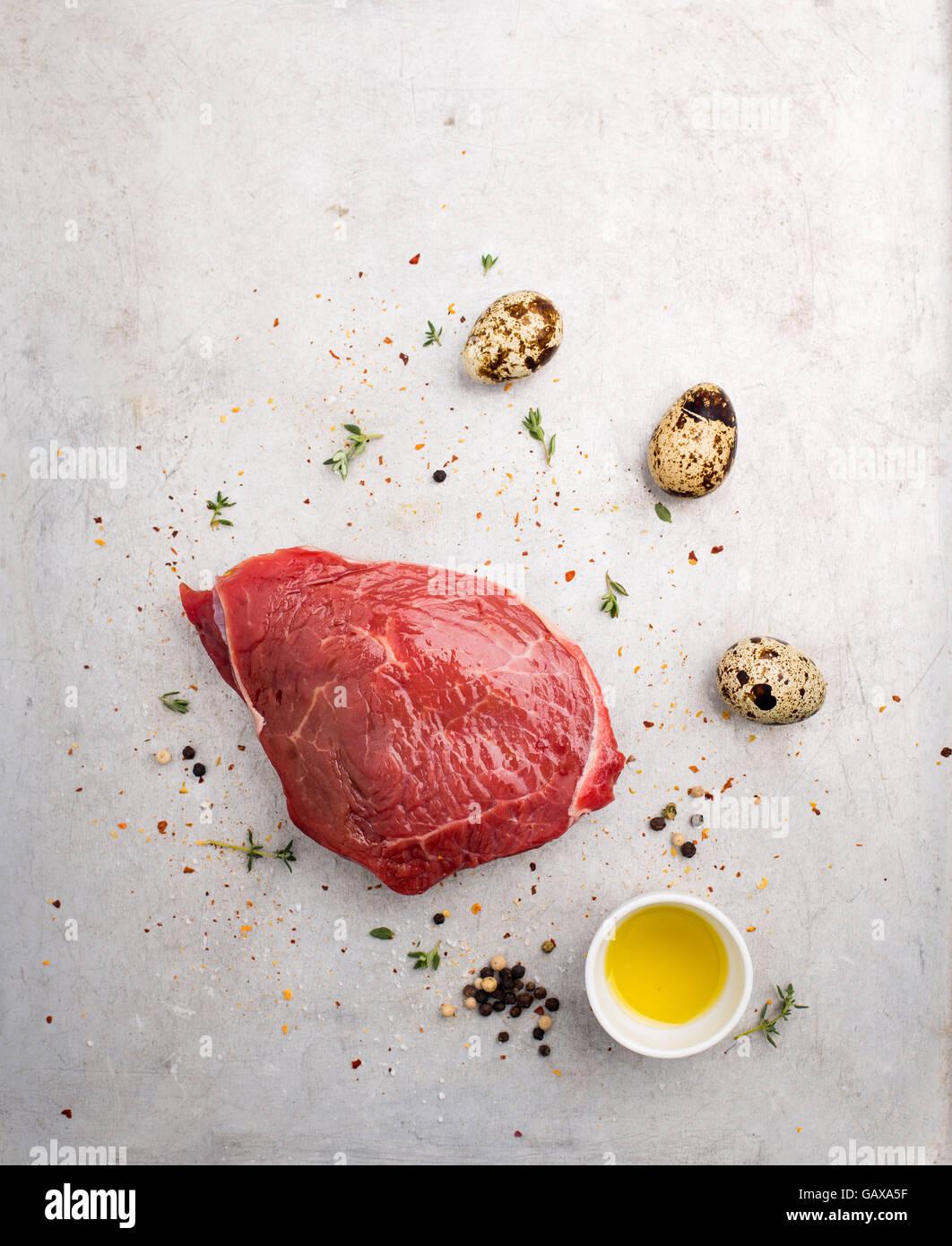Trozo de carne cruda y huevos de codorniz disparó desde arriba Imagen De Stock