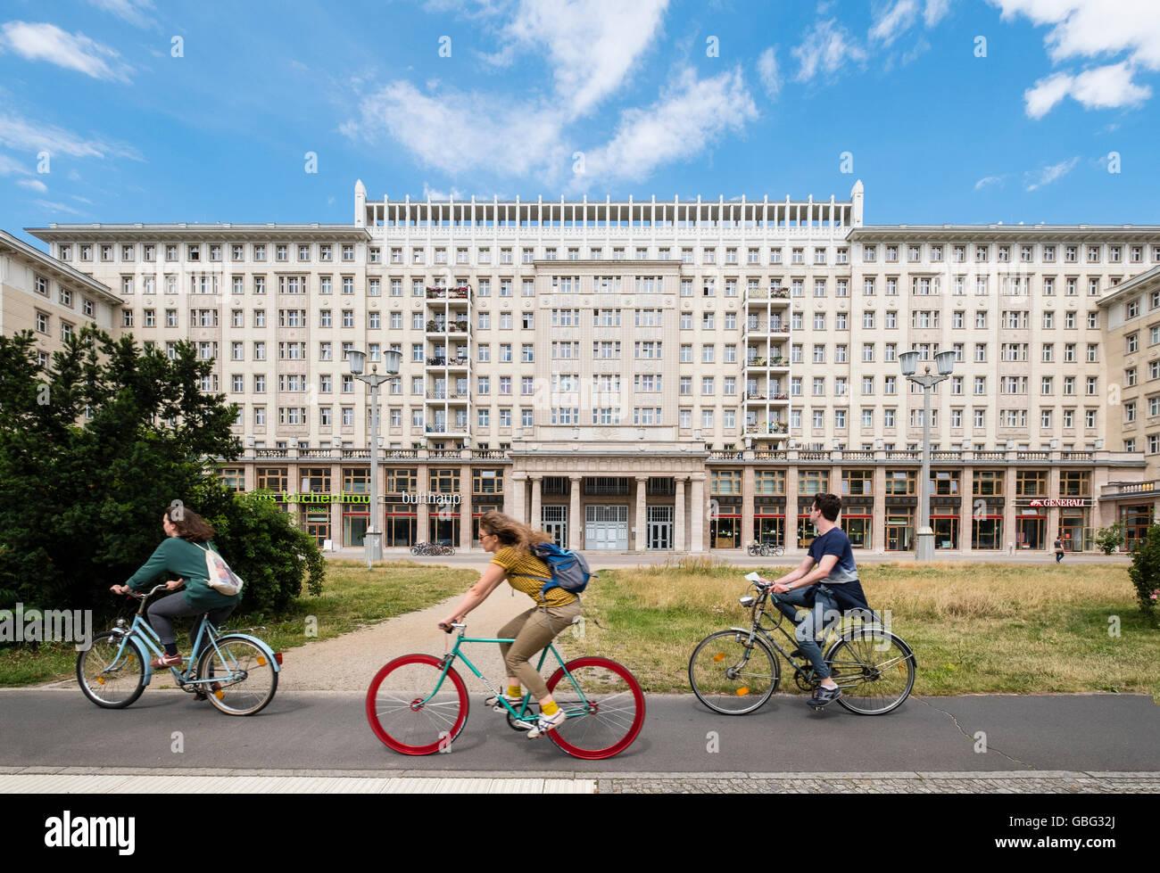 Los ciclistas ride socialistas históricos edificios de la antigua Alemania Oriental en Karl Marx Allee de Berlín Imagen De Stock