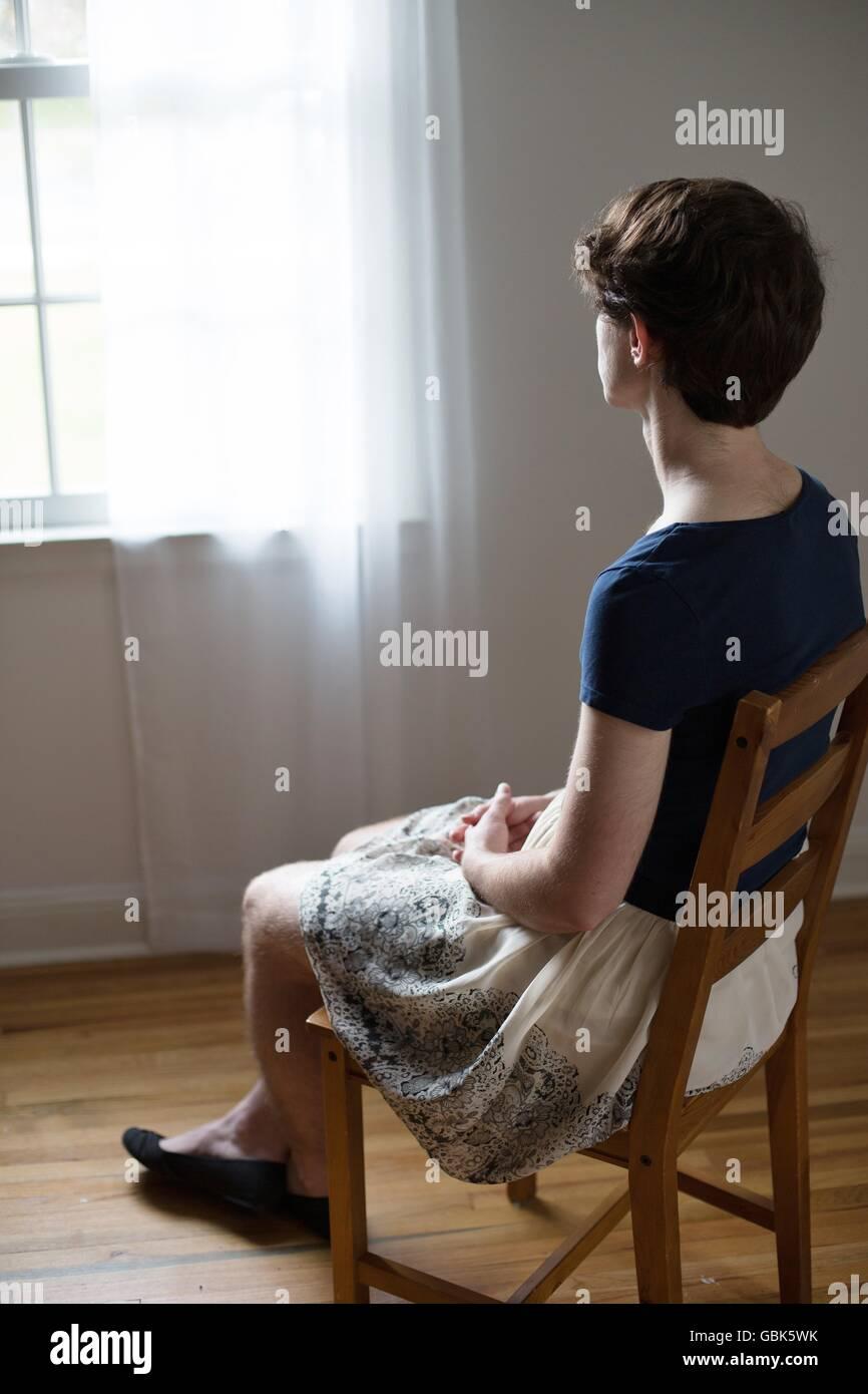 Un adulto joven transgénero como se ve desde un ángulo lateral, sentado en una silla y mirando por la ventana. Foto de stock