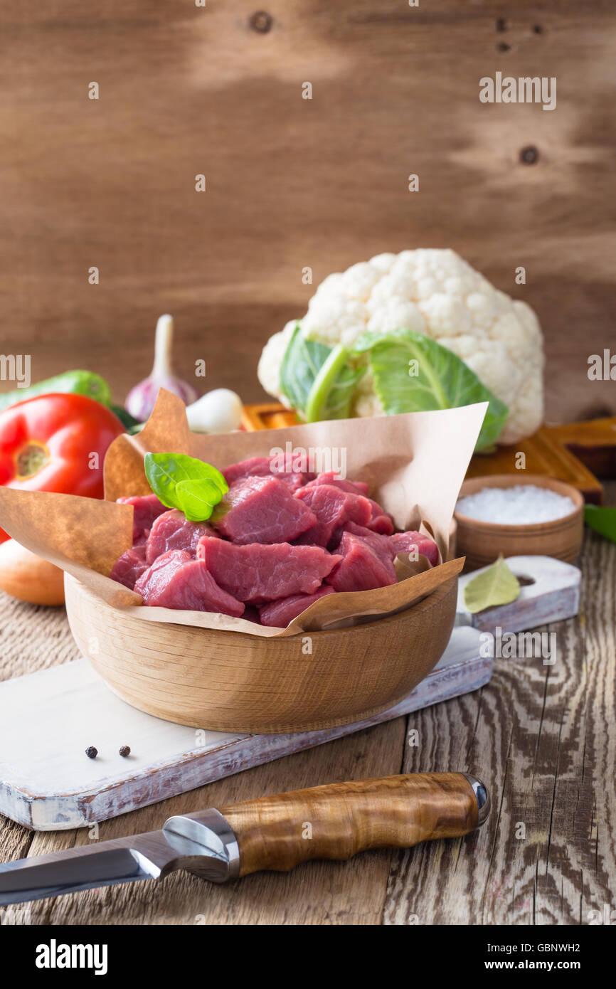 Ternera cruda cortada en trozos con verduras y otros ingredientes listos para cocinar en madera rústica mesa, concepto de cocina ecológica Foto de stock