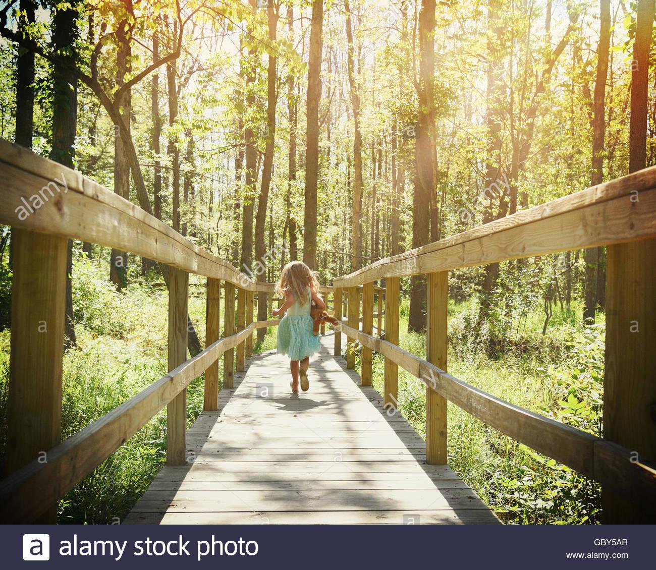 Un niño pequeño se ejecuta en un sendero de madera en los bosques con árboles de luz rayos para una Imagen De Stock