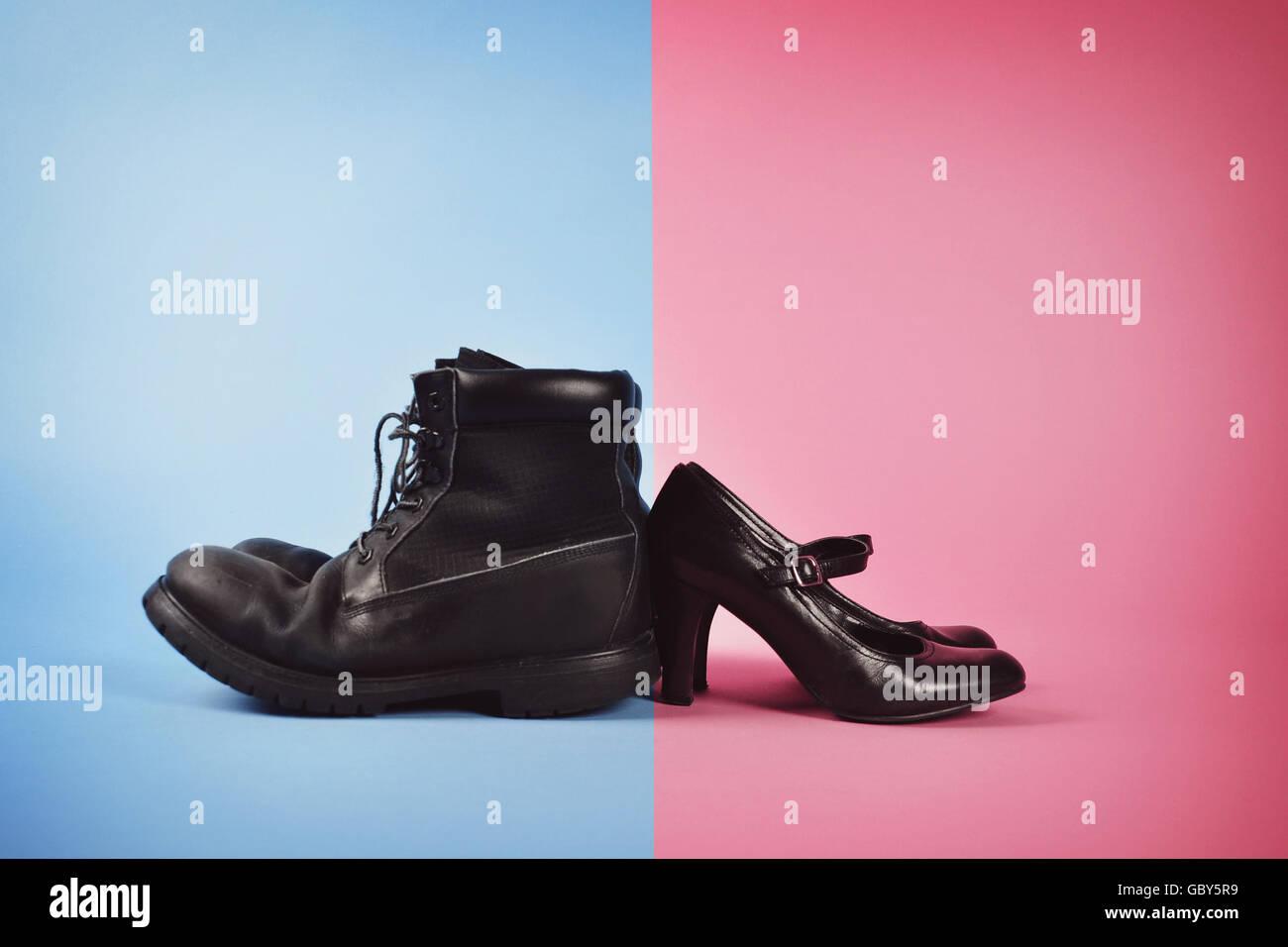 Un hombre de botas y tacones altos son de mujer contra un fondo azul y rosa aislado para una lucha de poder entre Imagen De Stock