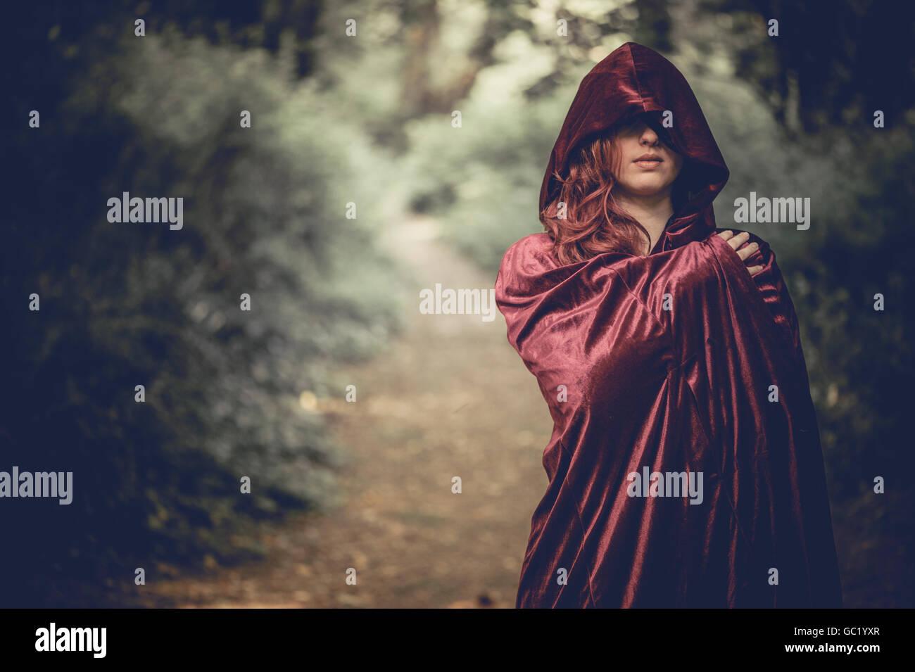 Mujer de misterio: Una joven pelirroja de pelo rojo mujer vestida de un cabo, oscureciendo su rostro, solo en un Foto de stock