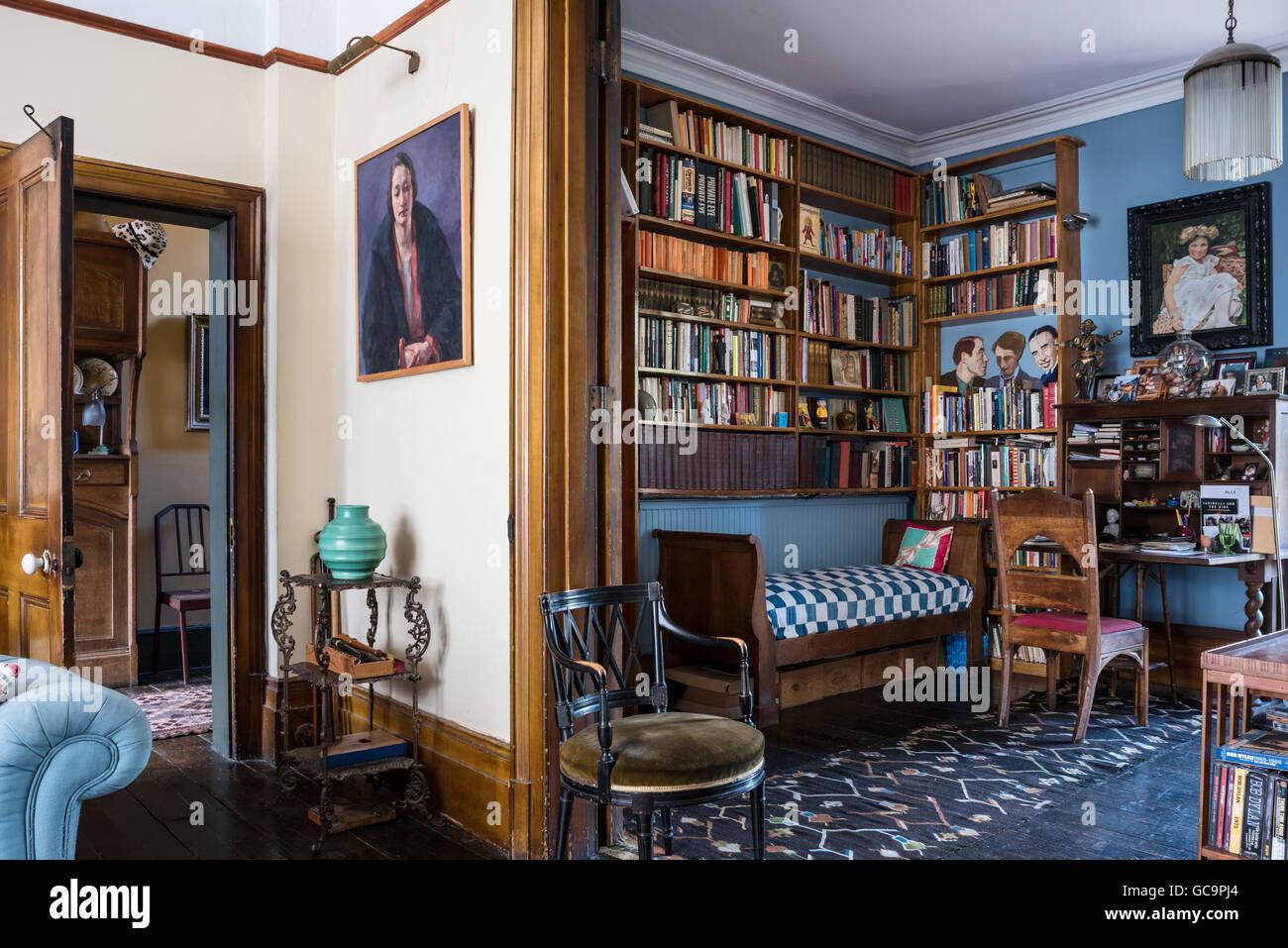 Estanterías de madera encima antique diván en casa estudio de Notting Hill, Londres, Reino Unido. Imagen De Stock