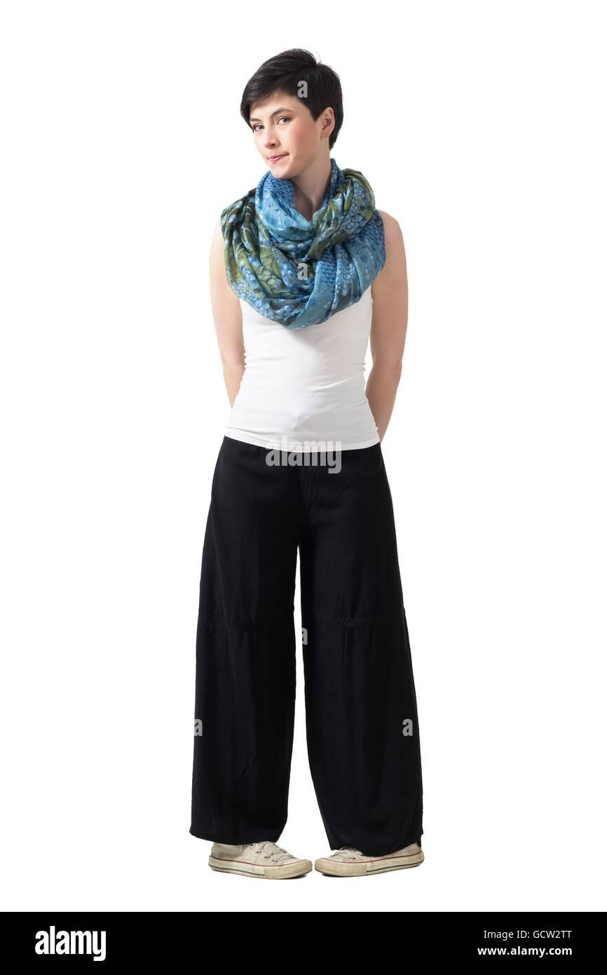 Tímido reacio joven mujer pelo corto en gran pantalones de pierna incómoda pose. Longitud de cuerpo completo Imagen De Stock