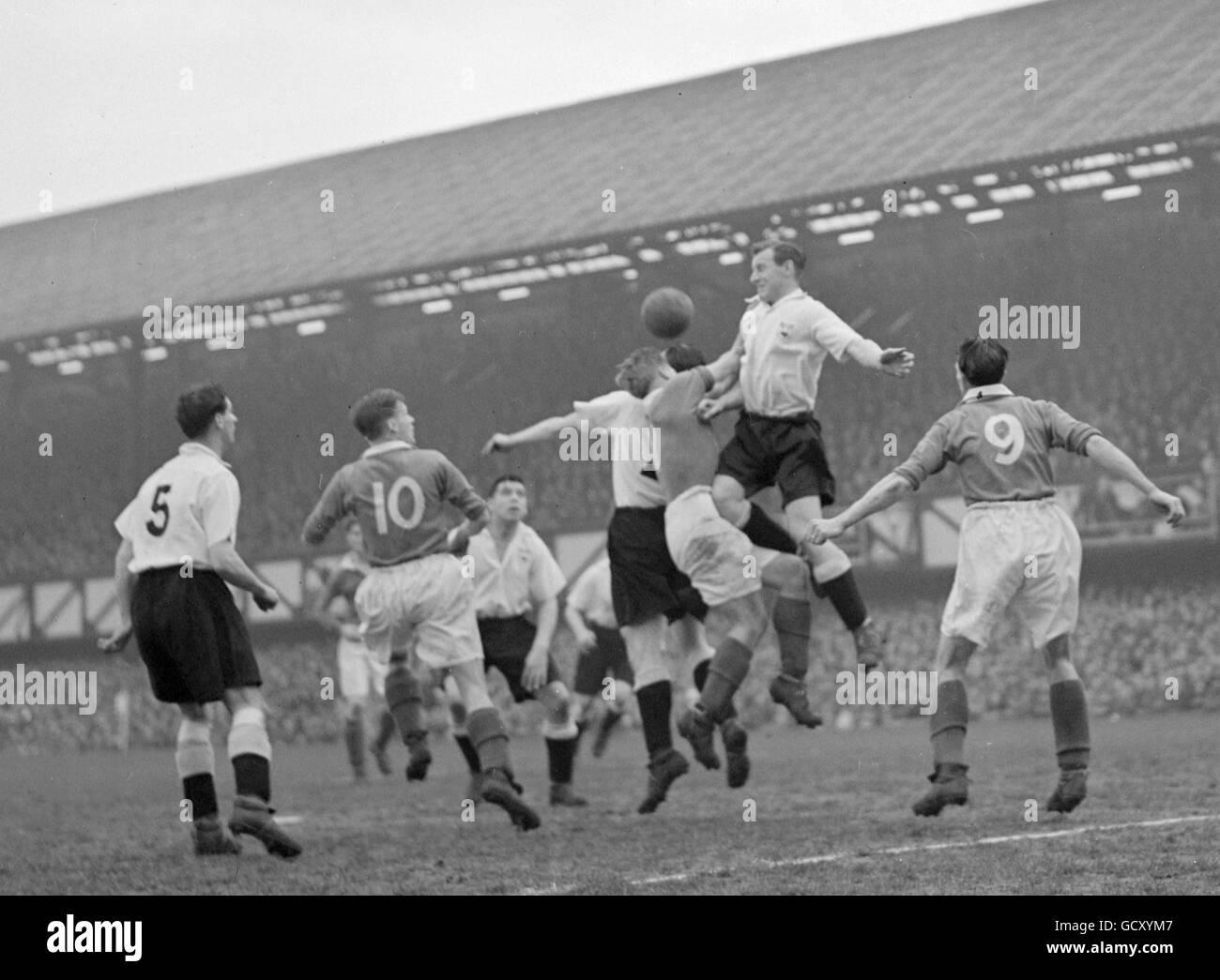 Jack Froggett de Portsmouth lucha con dos jugadores de Derby mientras que Derby Leon Leuty (No.5) y Ted Phillips de Portsmouth (N0,10) e Isaac Clarke (N0,9) Mira Foto de stock