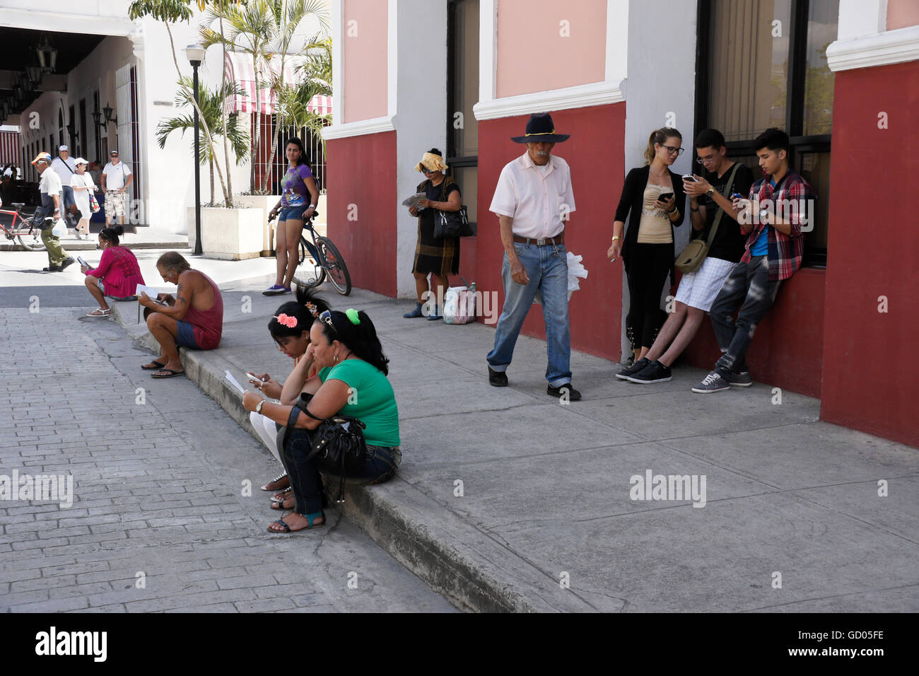 La gente recogiendo la señal Wi-Fi en teléfonos móviles, calle peatonal cerca de la Plaza de Armas, Imagen De Stock