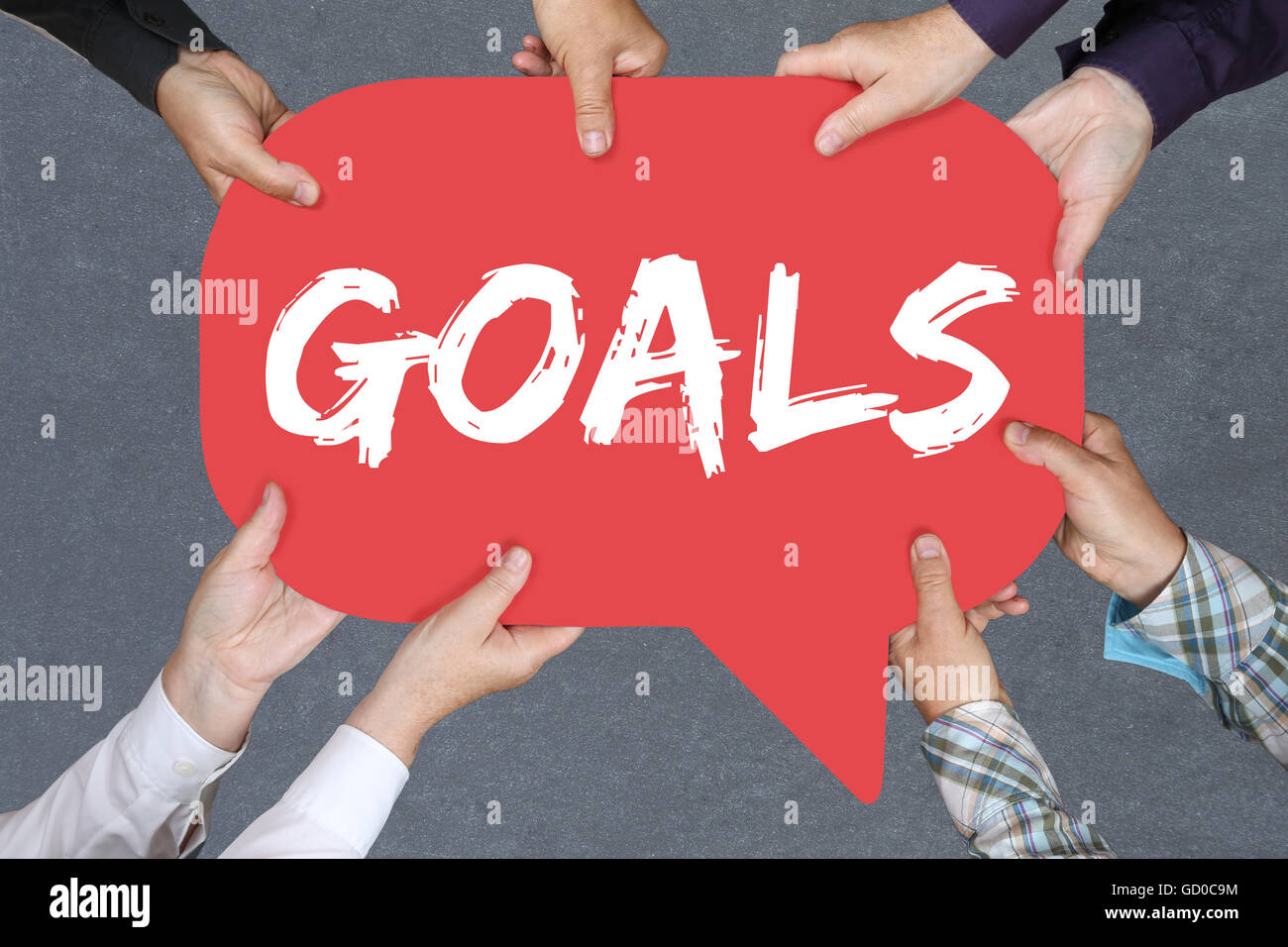 Grupo de personas sosteniendo con las manos la palabra objetivo metas a aspiraciones de éxito y crecimiento Imagen De Stock