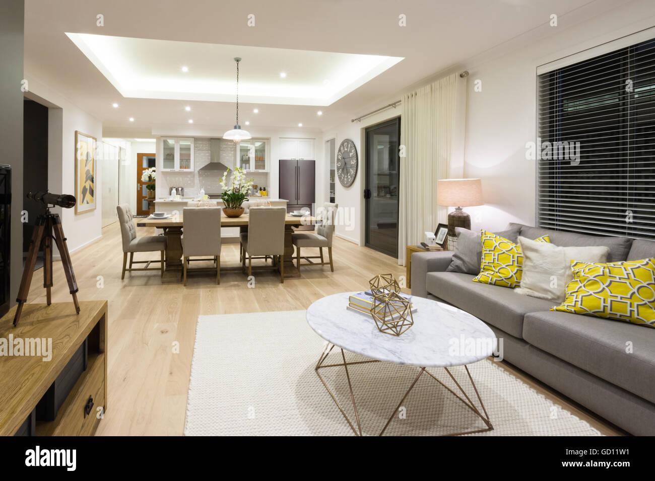 Salón moderno incluyendo sofás, sillas y mesas, al lado de la cocina ...
