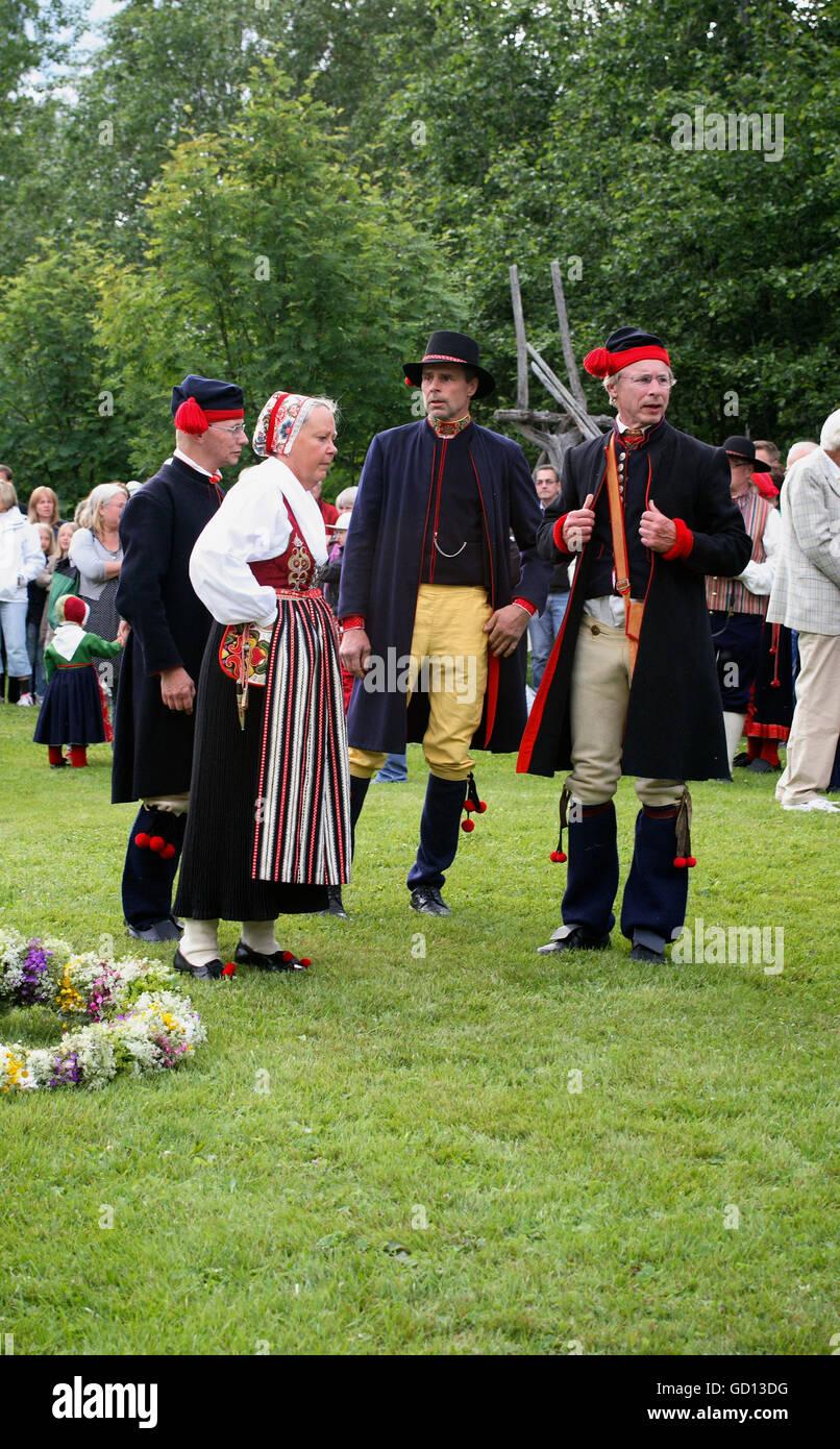 Las personas en trajes preparar las festividades en Midsummer Imagen De Stock