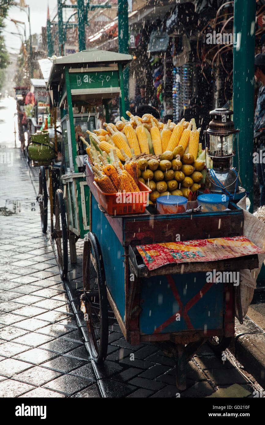 Puesto de comida de la calle con maíz asado bajo la lluvia, Ubud, Bali, Indonesia Imagen De Stock