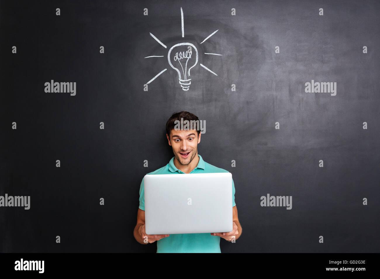 Feliz joven tiene una idea sobre la pizarra con fondo dibujado bombilla Imagen De Stock