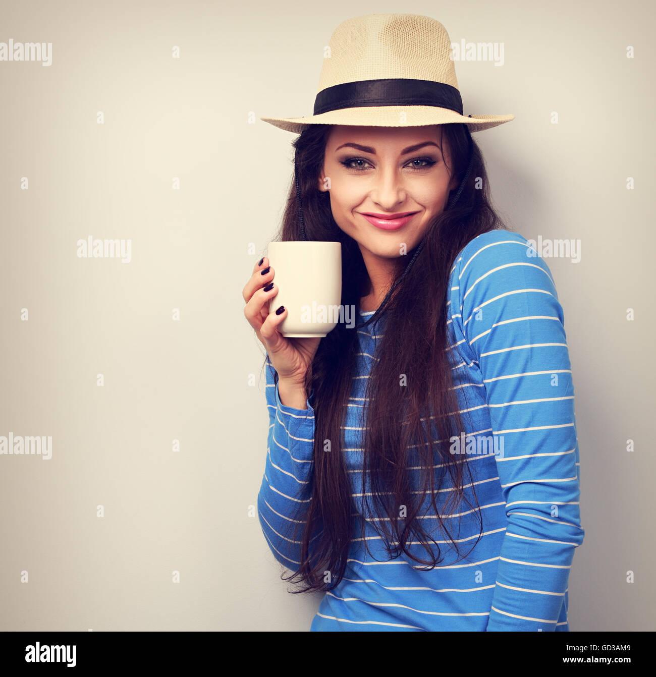 Lindo feliz mujer casual en el sombrero de paja sosteniendo en la mano una taza de té y sonriendo sobre fondo azul. Foto de stock