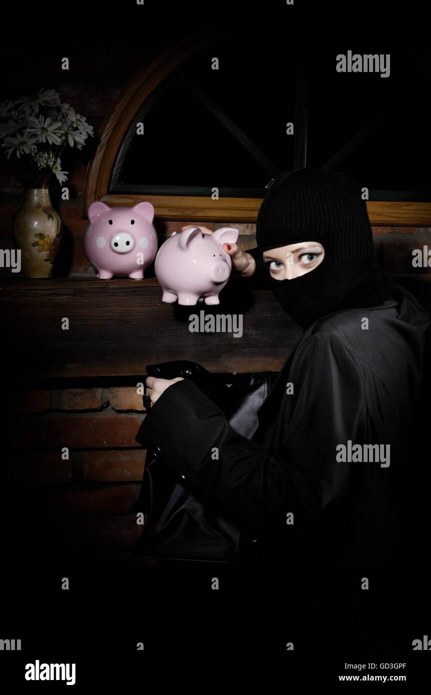Cogido por sorpresa ladrón robando hucha desde una casa de noche Imagen De Stock