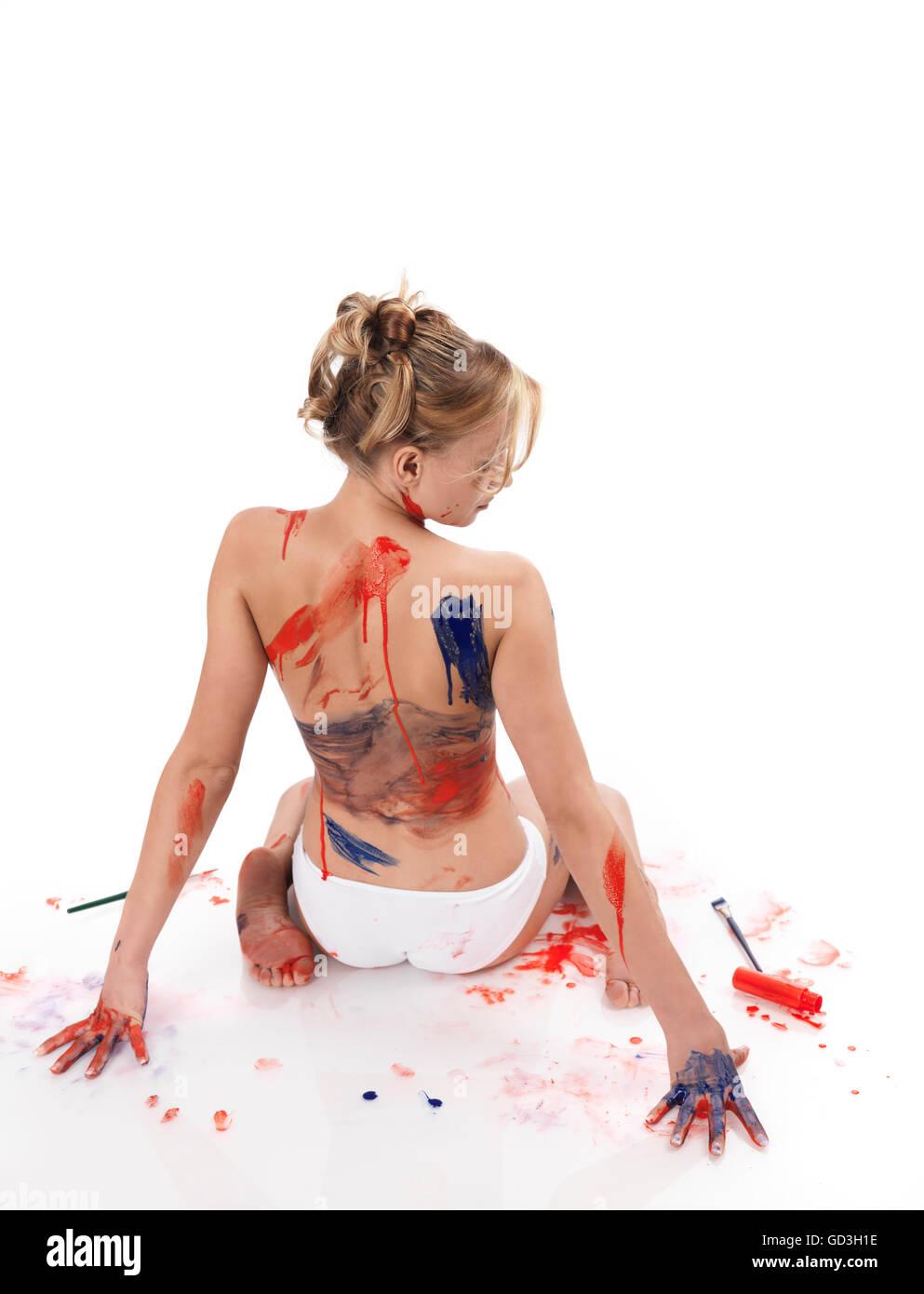 Cuerpo de mujer cubierto de salpicaduras de pintura roja y azul Imagen De Stock