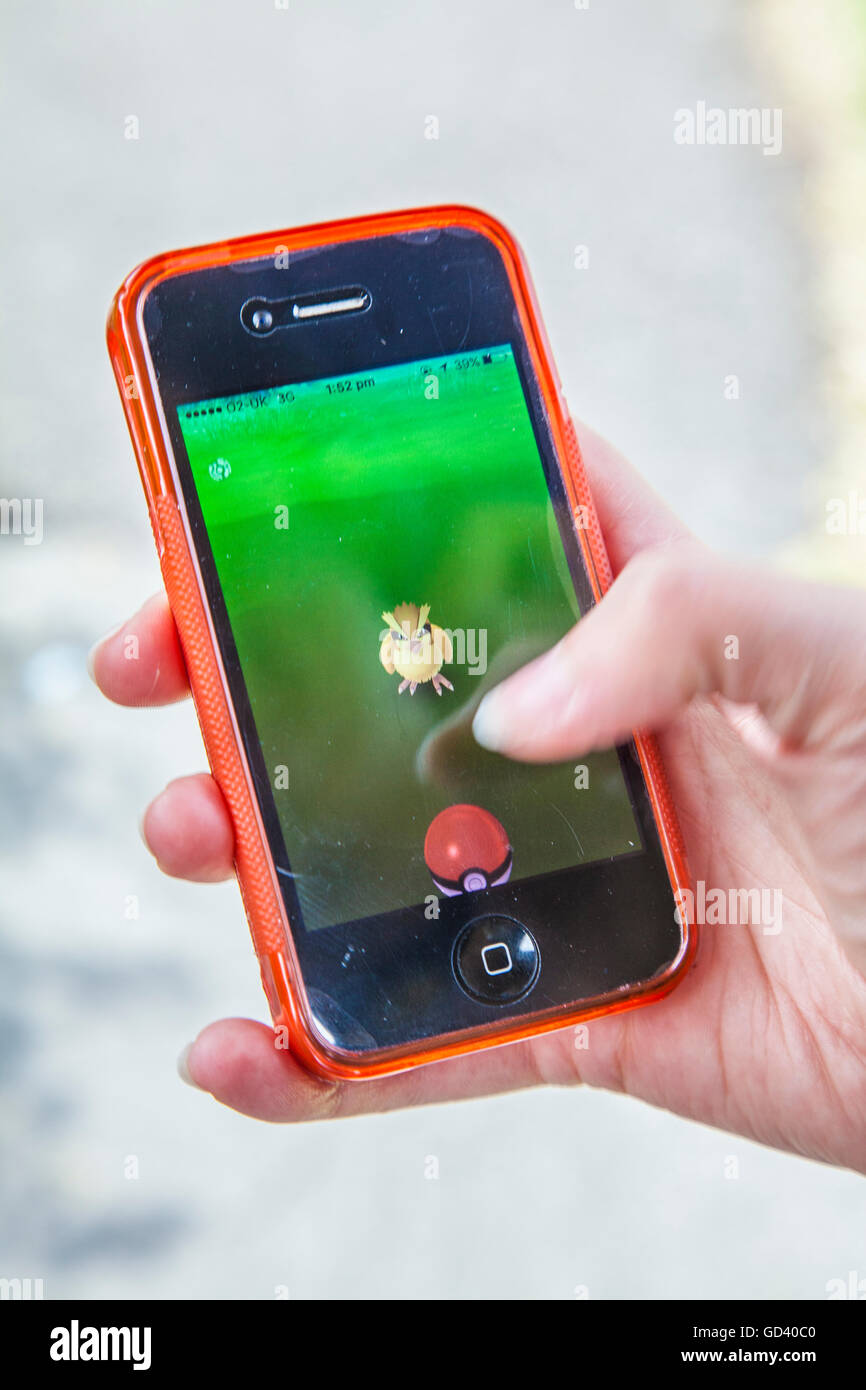 Un joven utiliza un iPhone para jugar Pokémon GO, la última realidad aumentada móvil app juego para Imagen De Stock
