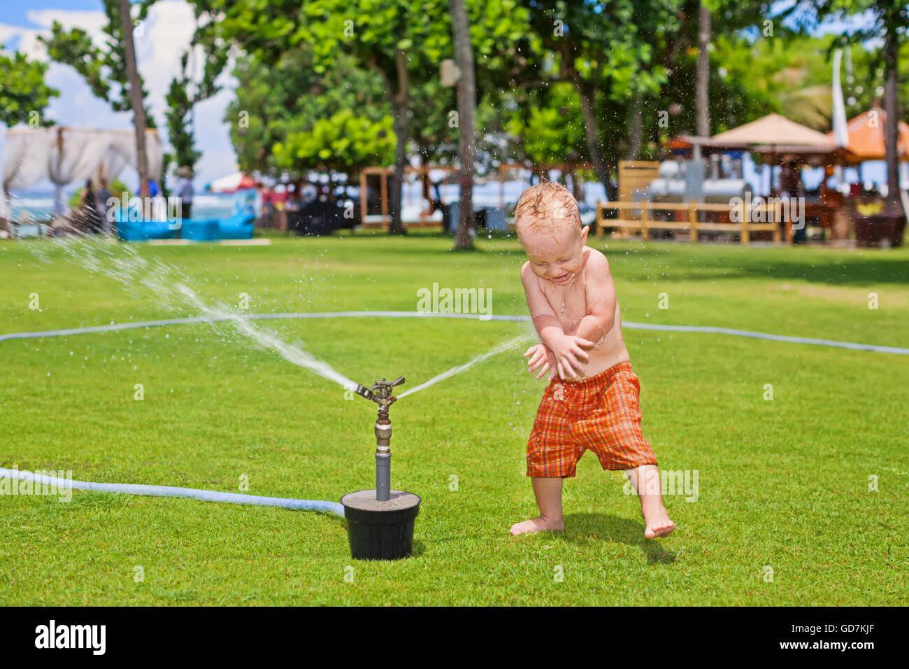 Niño feliz jugando con rociadores y salpicaduras de pulverización con la diversión bajo el agua cae Imagen De Stock