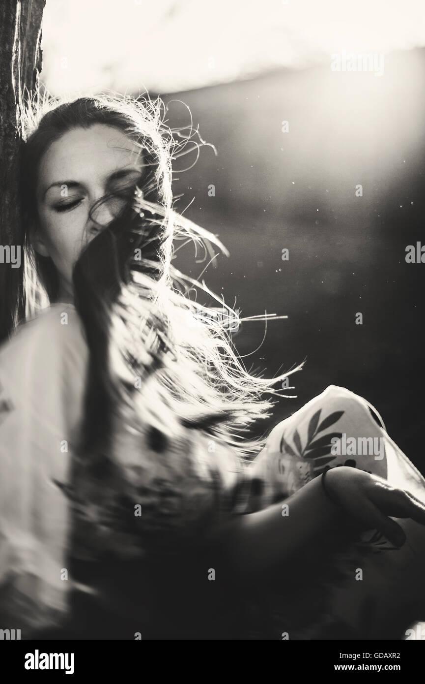 Retrato de la joven cubierto moviendo el cabello por el árbol de emplazamiento Imagen De Stock