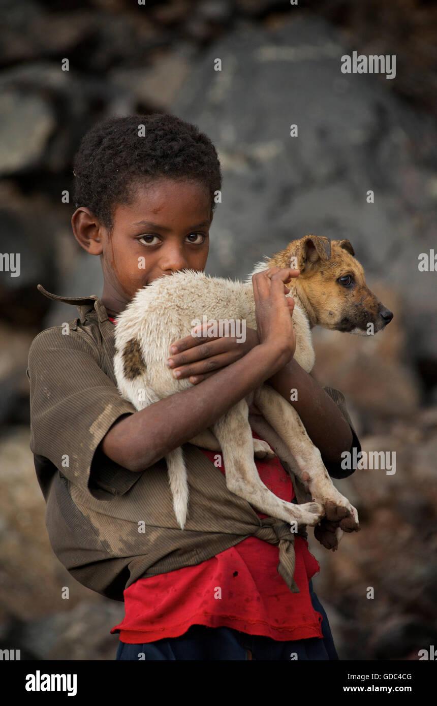 Niño sosteniendo etíope tímido perro mascota. La carretera a desembarcar, Etiopía. Imagen De Stock