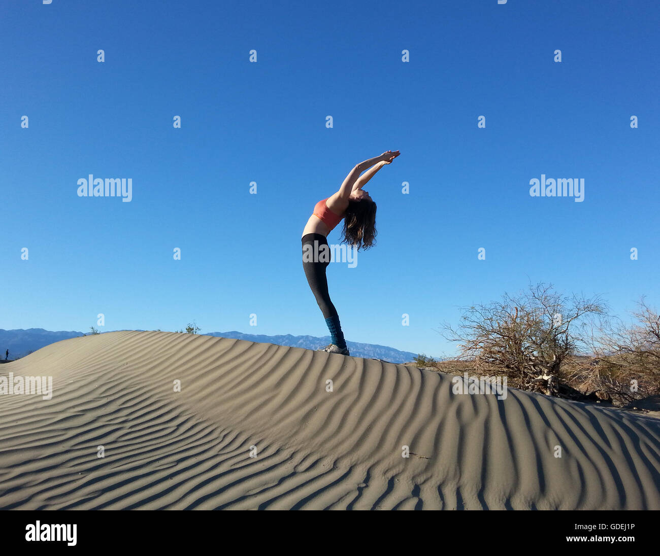 Las mujeres haciendo doblarla sobre la duna de arena, el Parque Nacional Valle de la Muerte, California, Estados Imagen De Stock