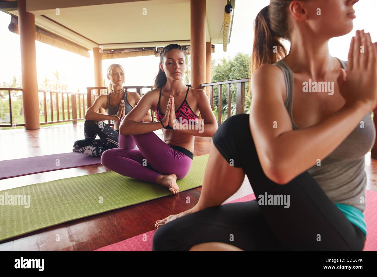 Foto de joven mujer practicando yoga en torcer la columna vertebral posan con sus manos juntas. Los jóvenes Imagen De Stock