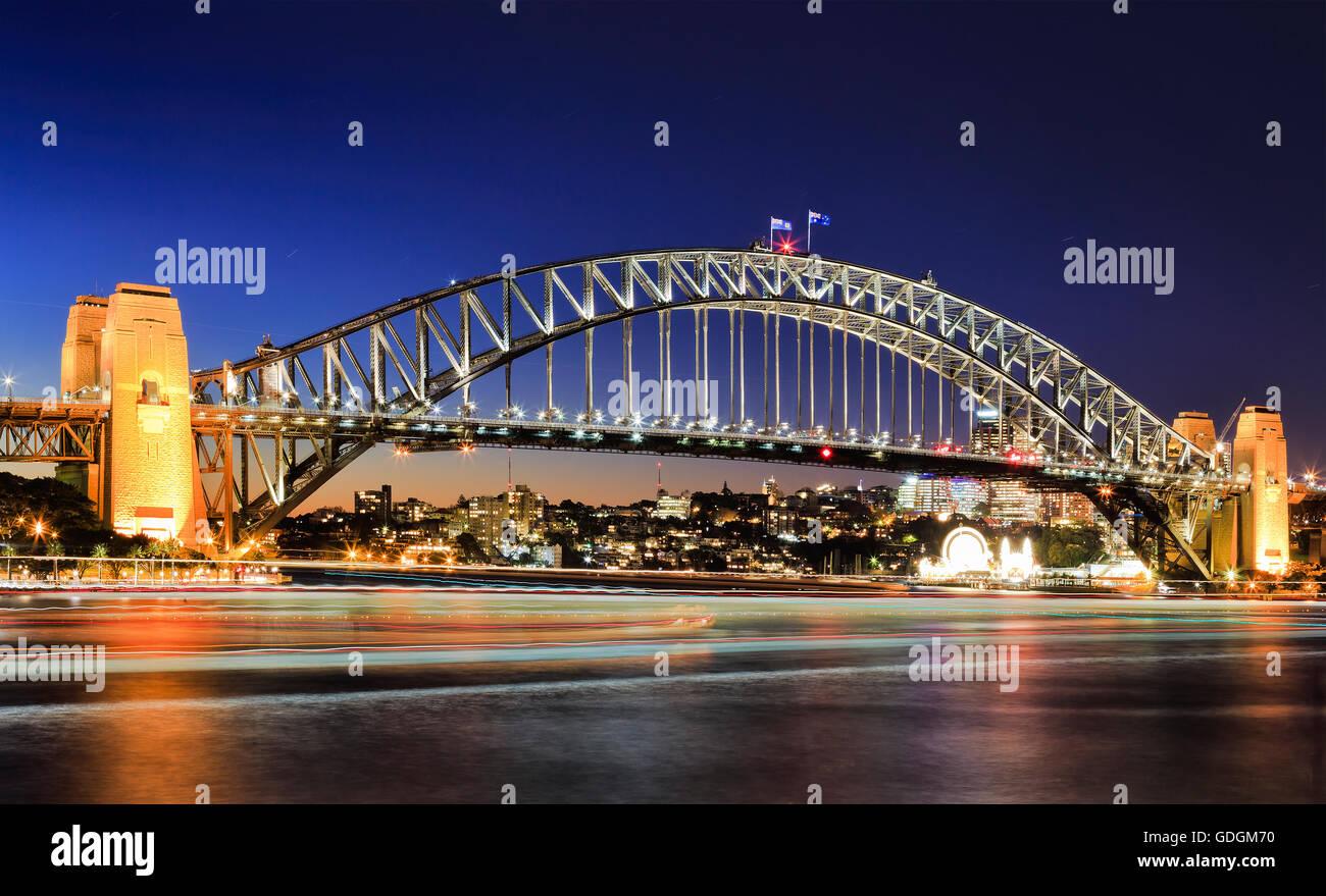 Vista lateral del Sydney Harbour Bridge hito arquitectónico al atardecer. Arco del puente iluminado reflejando Imagen De Stock