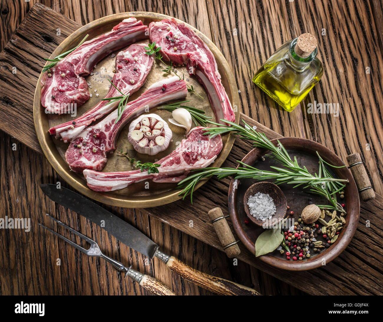 Materias chuletas de cordero con ajo y hierbas en la mesa de madera antigua. Imagen De Stock