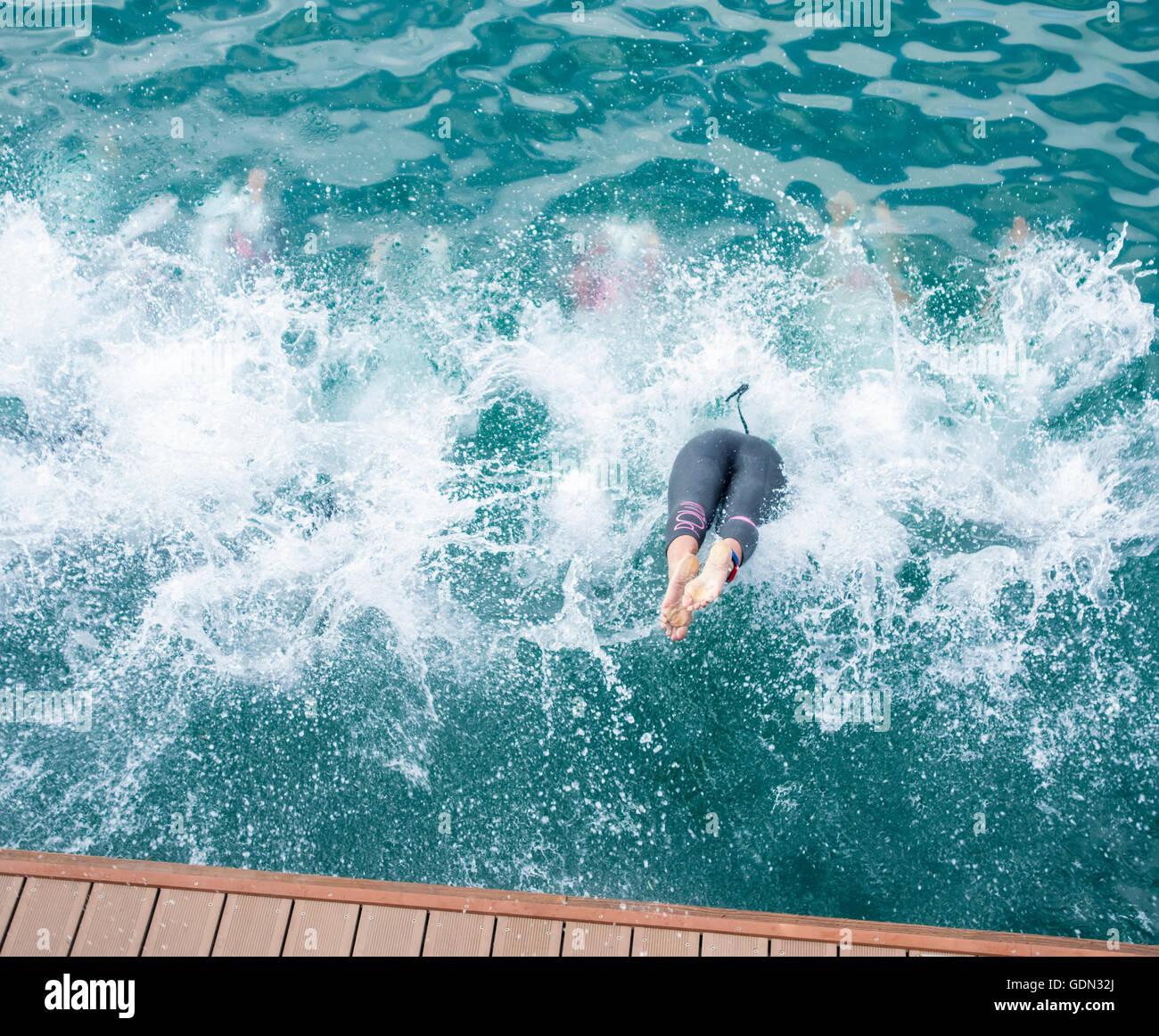 Triatletas femeninas de zambullirse en el mar al inicio de la carrera de triatlón. Imagen De Stock