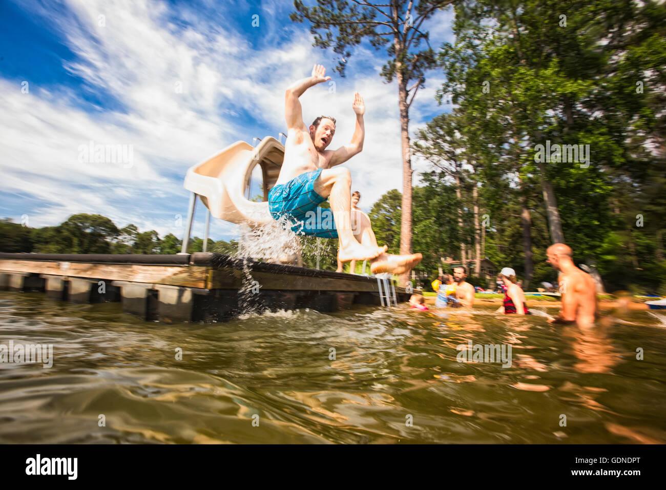 Hombre saltando desde el muelle diapositiva en el Lago Jackson, Georgia, EE.UU. Imagen De Stock