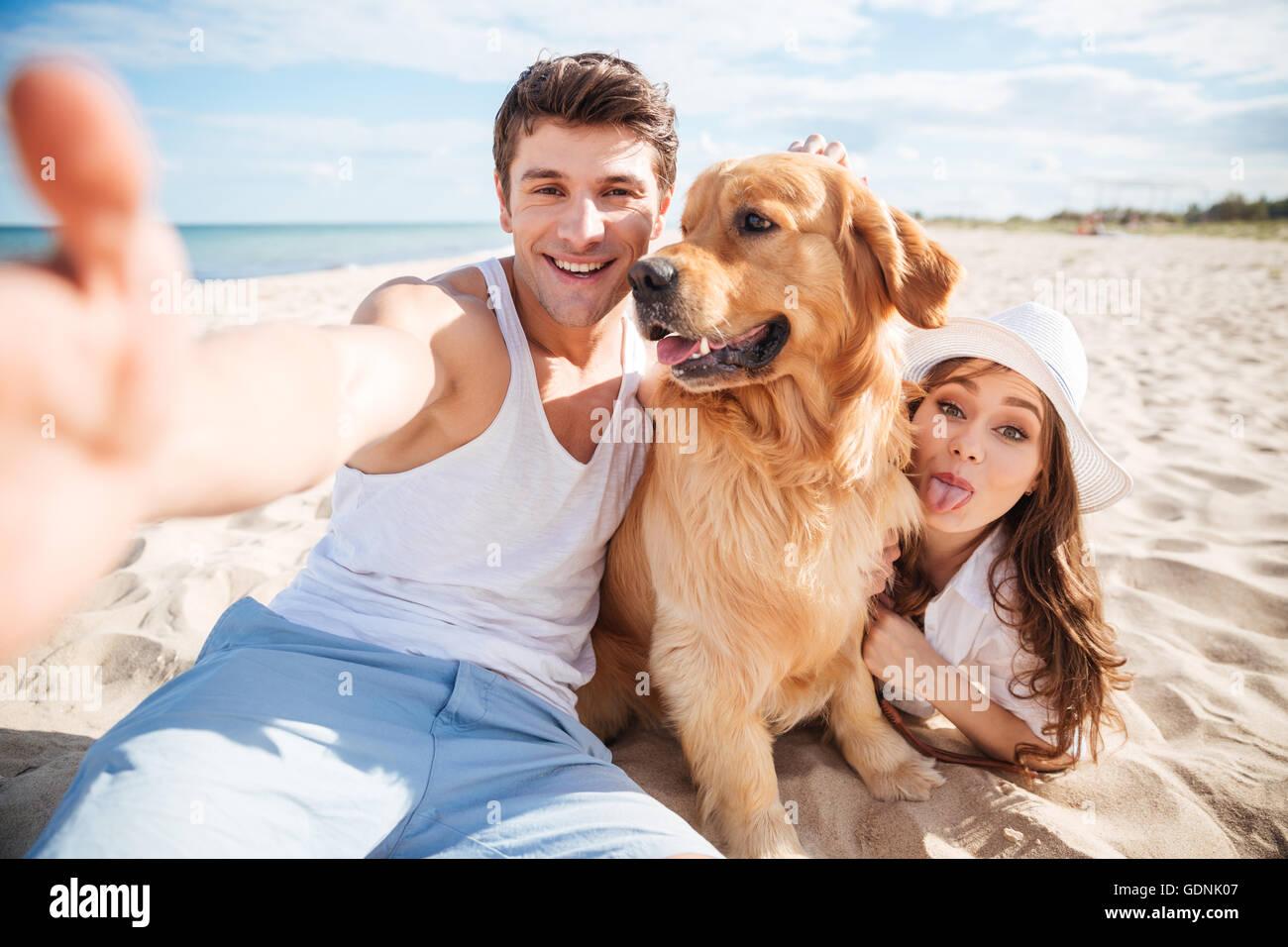 Feliz pareja joven con perro teniendo un selfie en la playa. Imagen De Stock