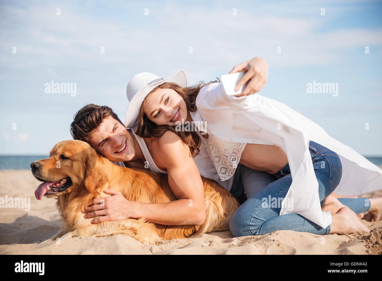 Sonriente joven pareja con perro selfie hablando con el smartphone en la playa Imagen De Stock