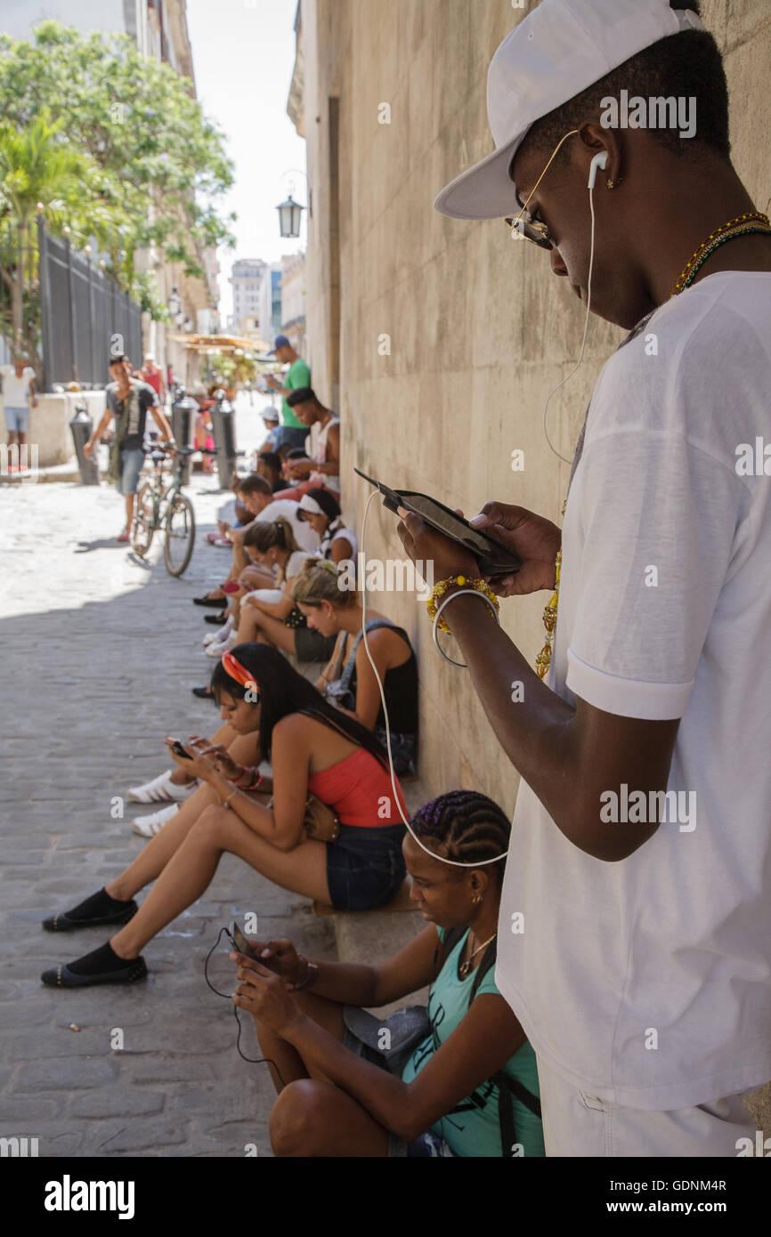 Los jóvenes utilizando un hotspot wifi público exterior en la calle Obispo, La Habana, Cuba Imagen De Stock