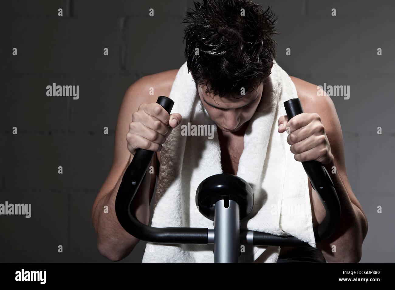 Hombre con máquina de ejercicio mirando hacia abajo Imagen De Stock