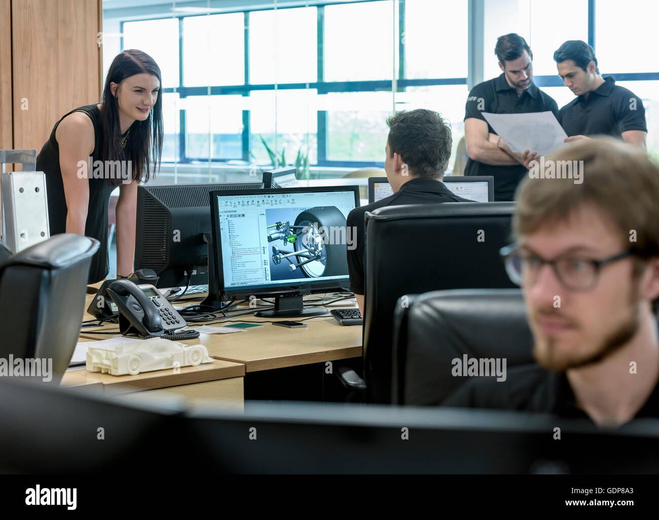Ingenieros trabajan con imágenes de diseño CAD en la fábrica de automóviles de carreras Imagen De Stock
