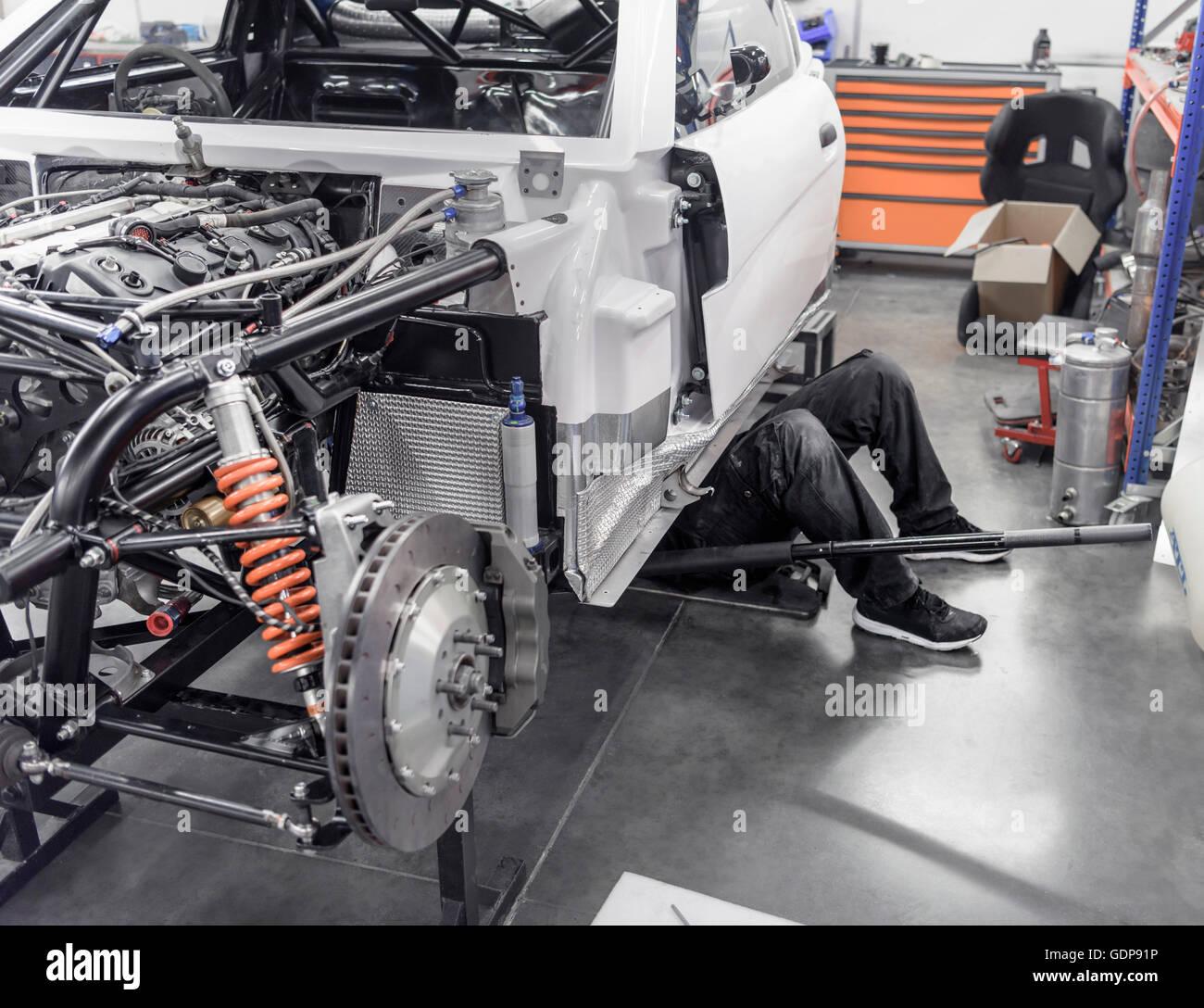 Ingeniero que trabaja bajo del coche en la fábrica de automóviles de carreras Imagen De Stock