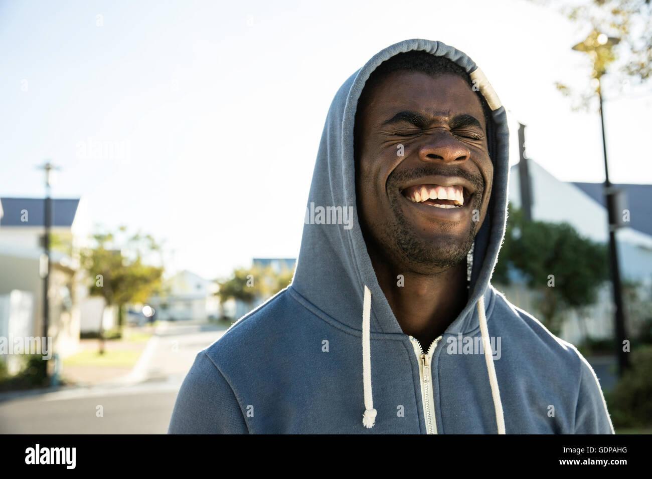 Retrato del hombre vestido con sudadera con capucha ojos cerrados riendo Imagen De Stock