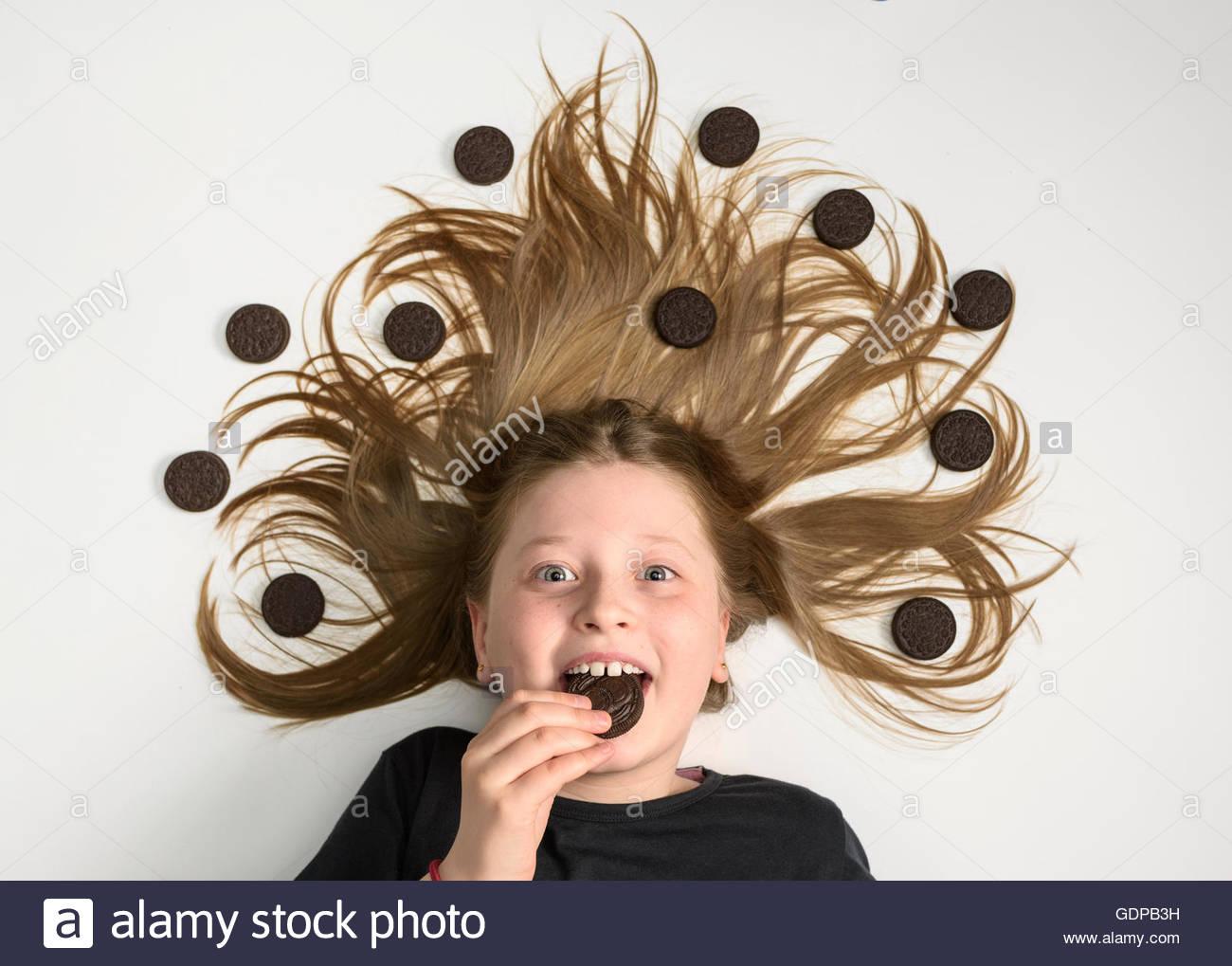 Retrato de chica con cabello largo rizado acostado sobre la espalda de comer chocolate cookie Imagen De Stock