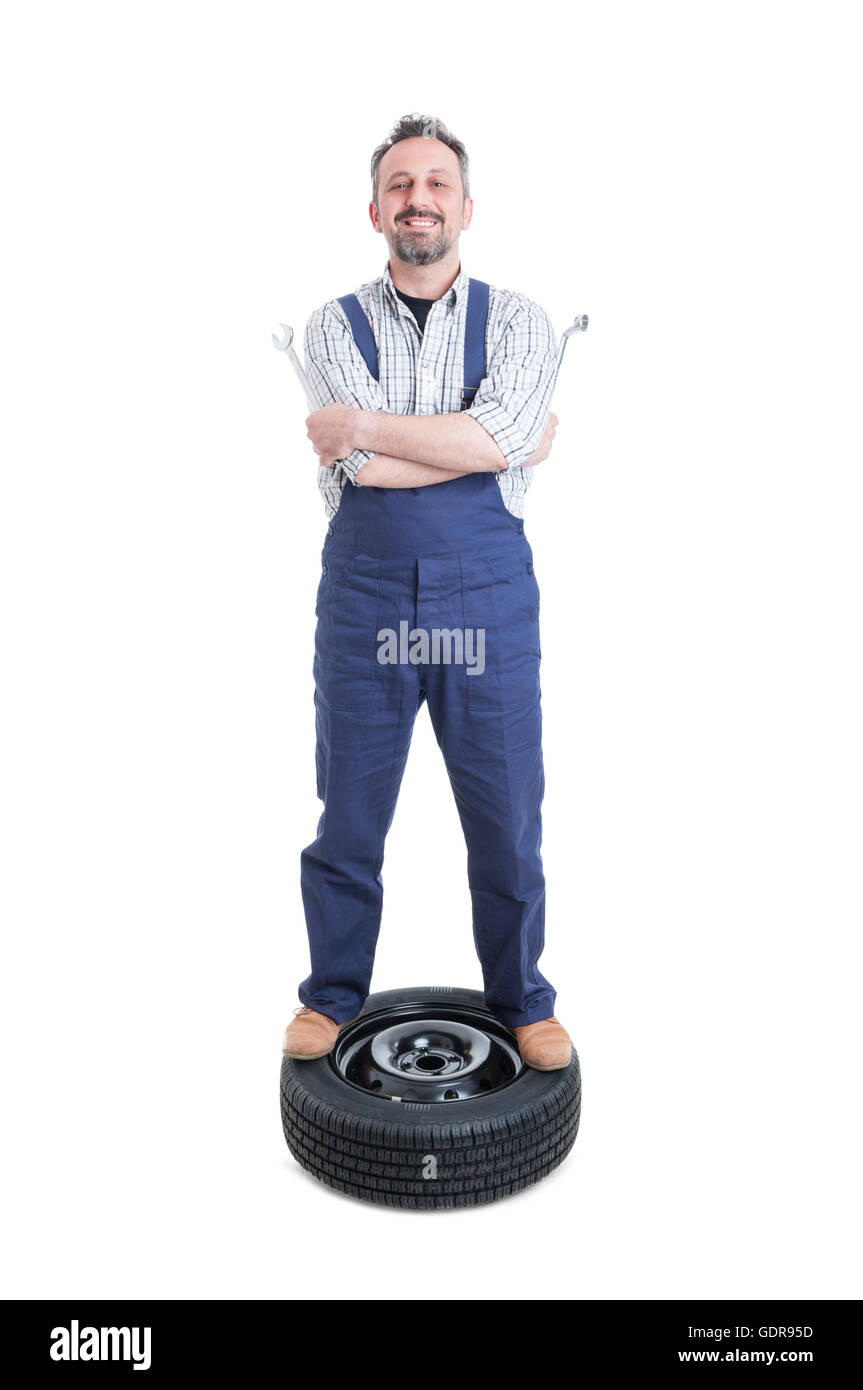 Feliz mecánico con actitud positiva de pie en la rueda mirando seguros aislado sobre fondo blanco. Imagen De Stock