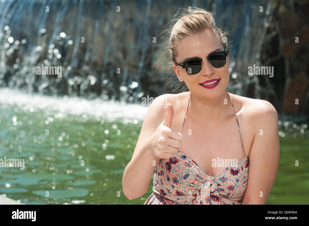 Señora atractiva usando tonos mostrando pulgar arriba gesto con cascada y copiar texto espacio de fondo Imagen De Stock