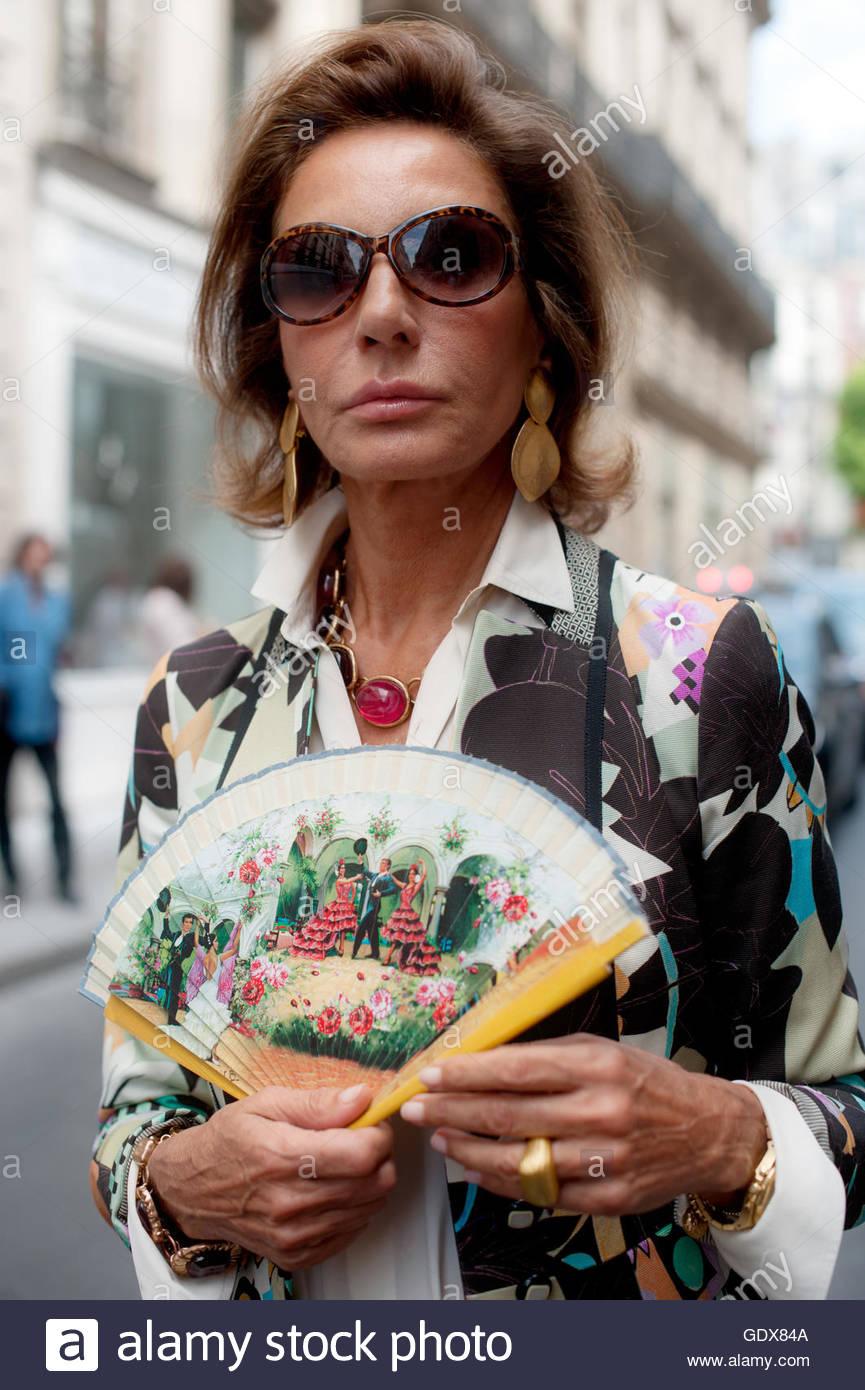 Una mujer con un abanico de mano durante la Semana de la moda de Alta Costura de París en la Rue Cambon. Imagen De Stock