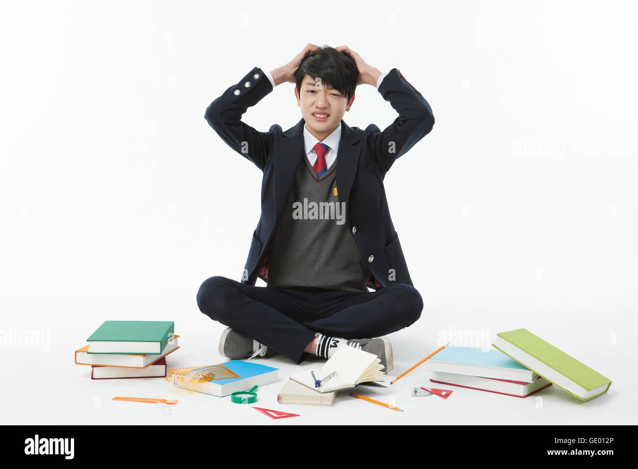 Escuela estresante muchacho sentado con libros Imagen De Stock
