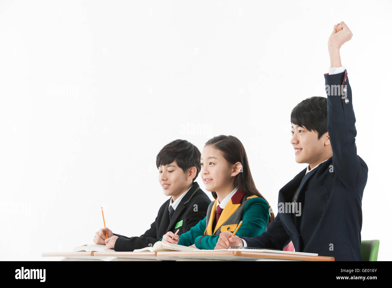 Vista lateral de la escuela retrato joven levantando su mano y sus amigos Imagen De Stock
